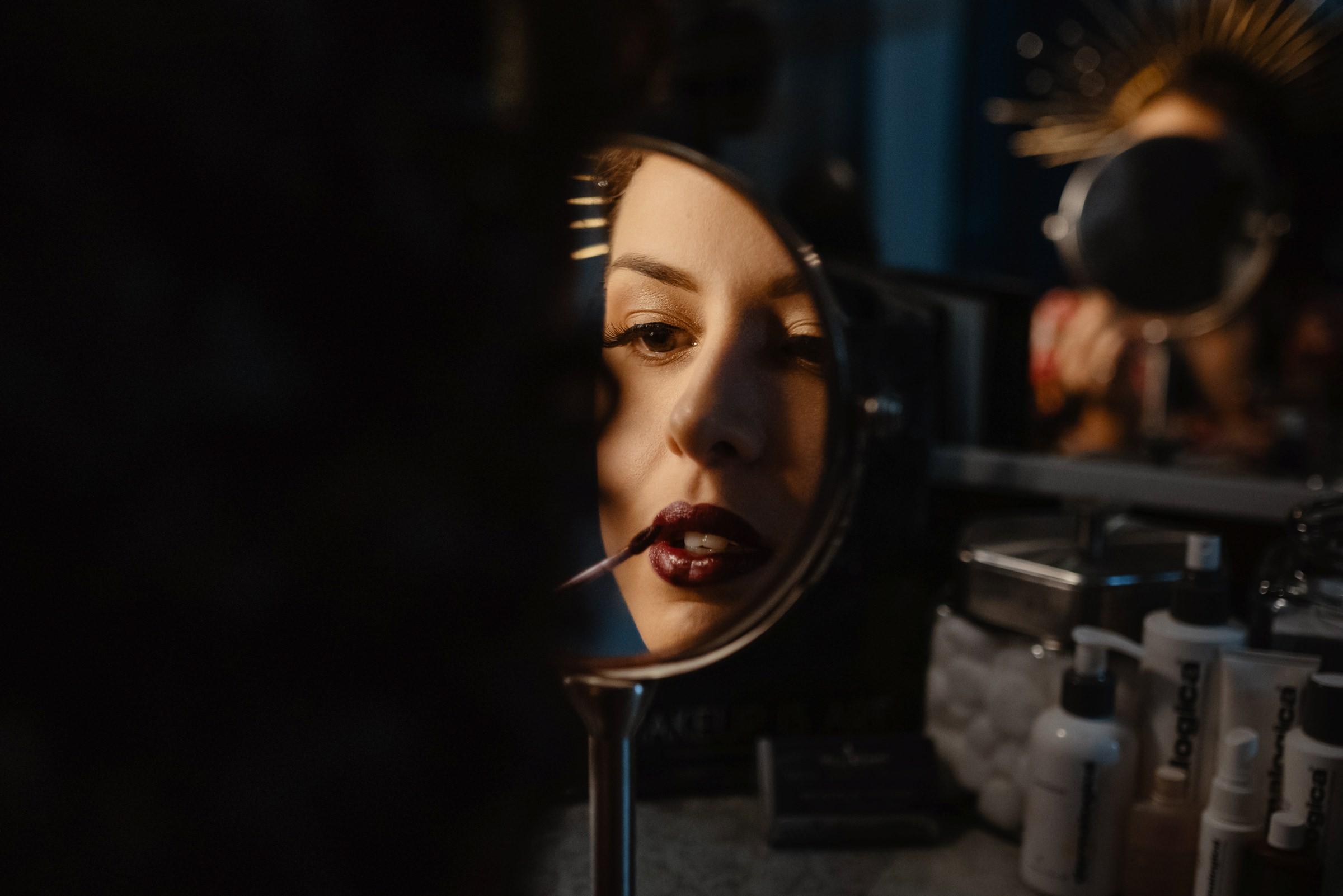 bride putting her lipstick on in teh mirror-new orleans-austin-houston-wedding- photo by Dark Roux