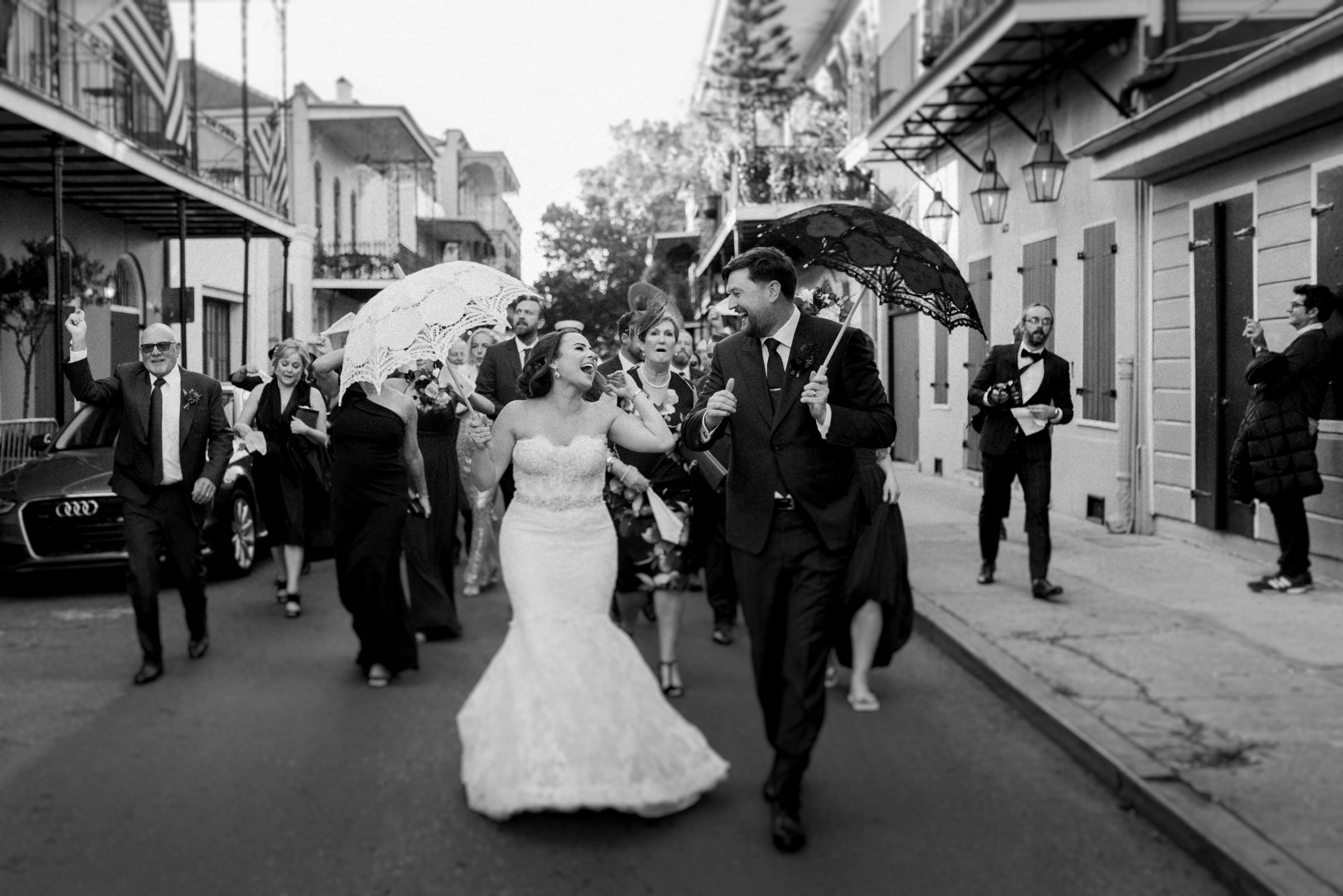 couple happily walking down the new orleans street in wedding parade- photo by Dark Roux