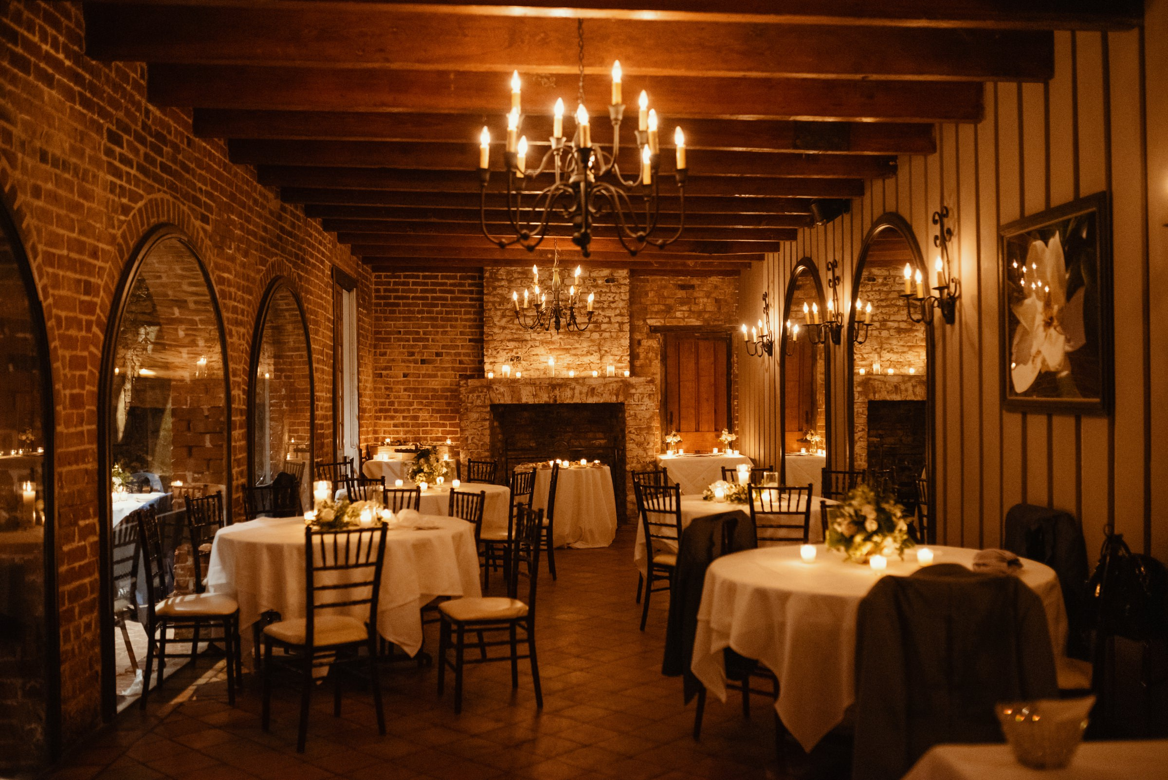 Dining room with chandeliers and candlelight - photo by Dark Roux