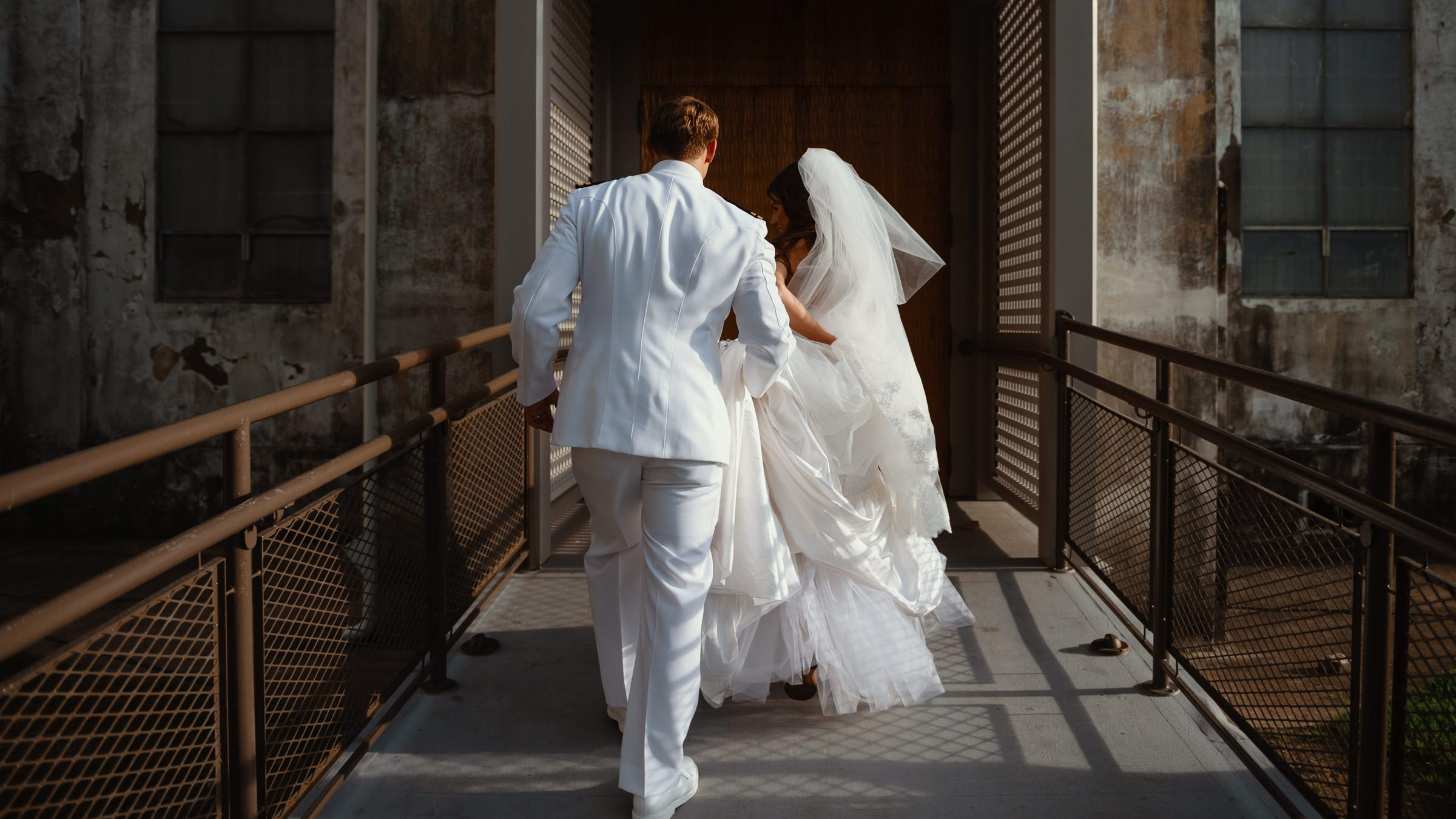 groom carrying his brides dress in behind her-new orleans-austin-houston-wedding- photo by Dark Roux