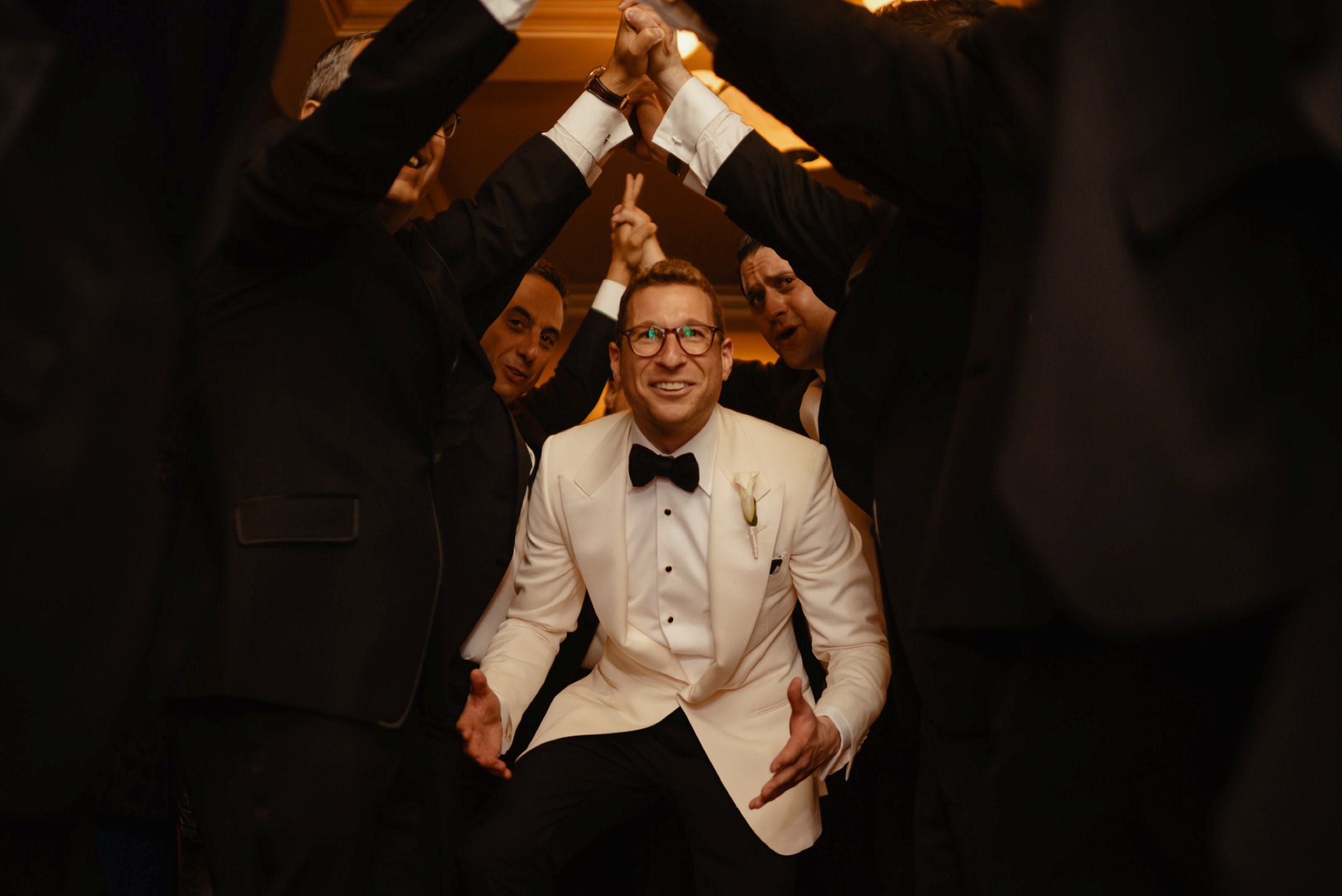 groom in white tuxedo dancing under arms of groomsmen-groom-being-held-up-in-the-air-by-all-the-groomsmen-at- photo by Dark Roux