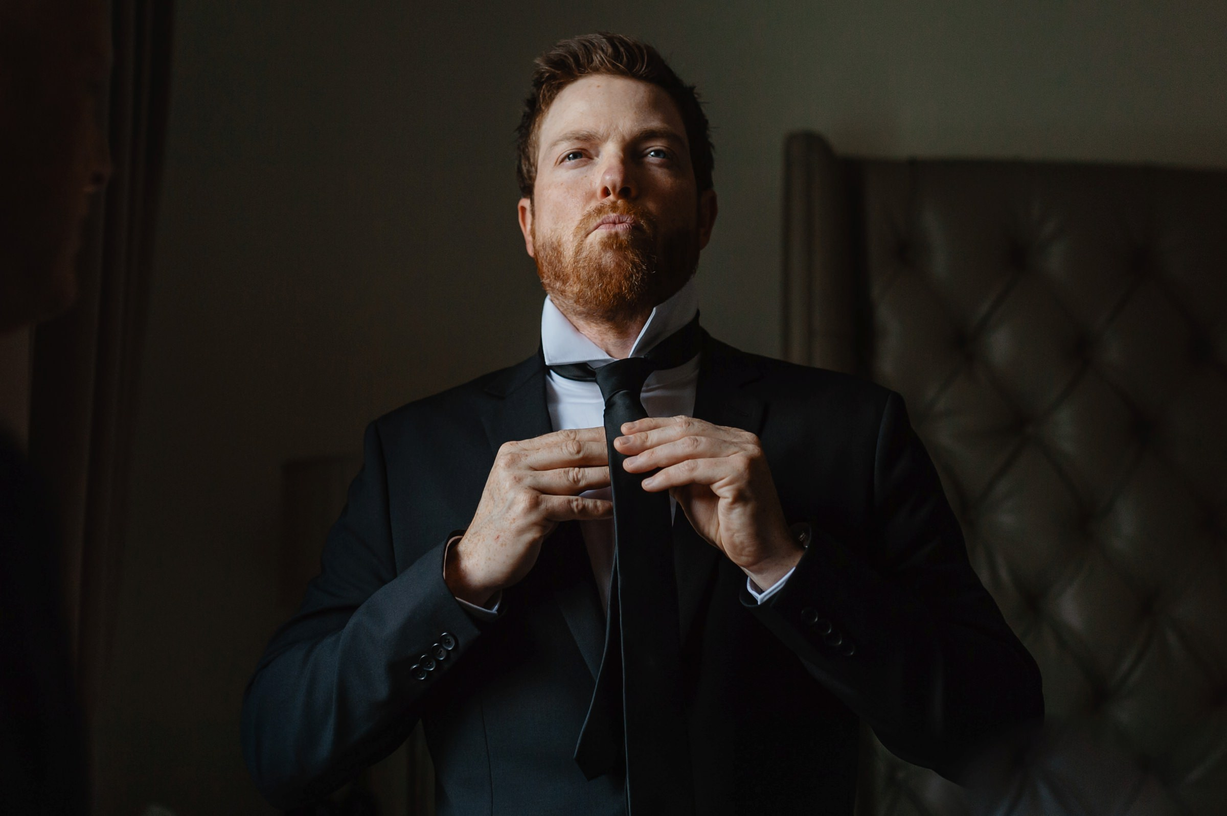 groom putting tie on-new orleans-austin-houston-wedding- photo by Dark Roux