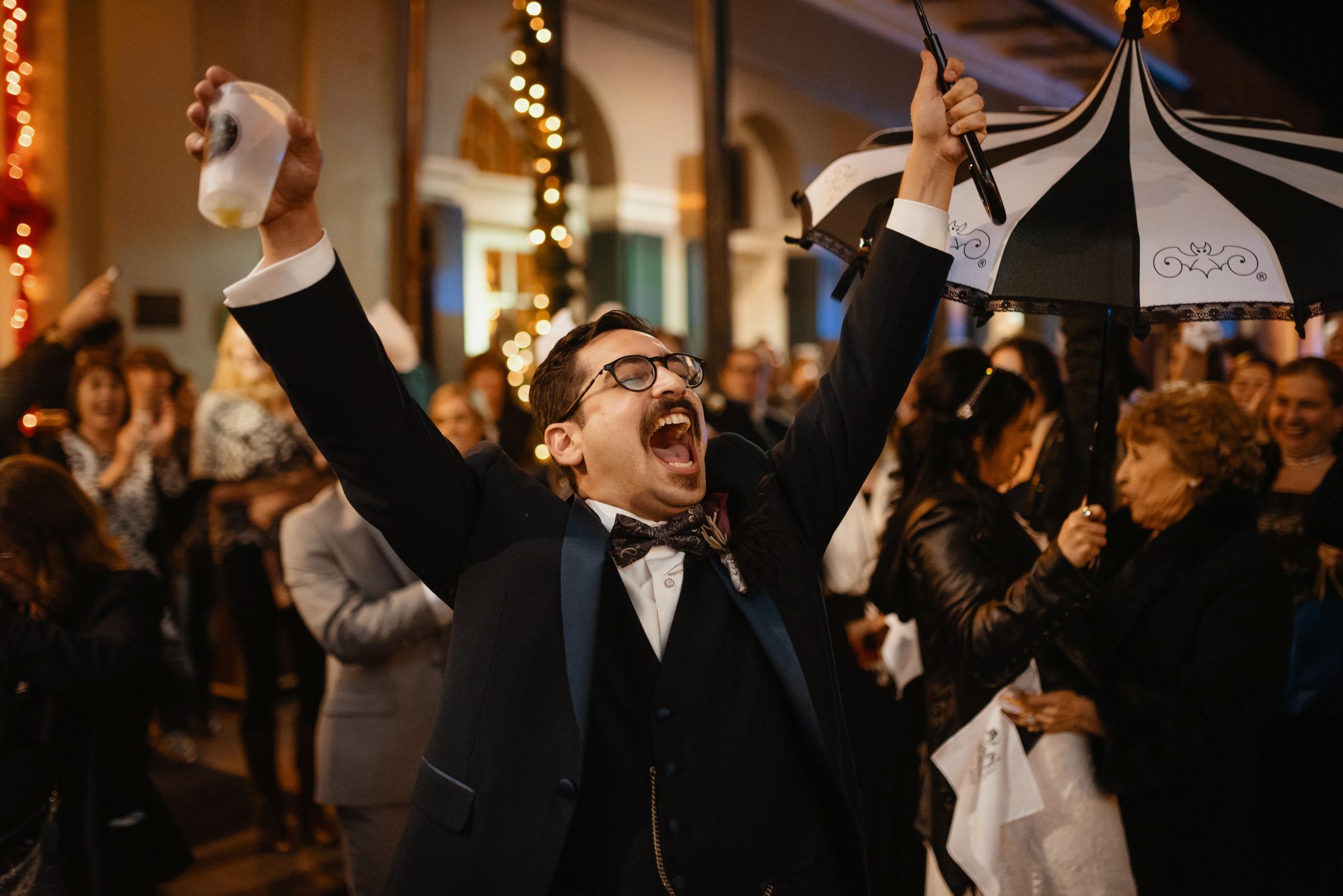 Groom raises glass in celebration at Austing wedding, photo by Dark Roux