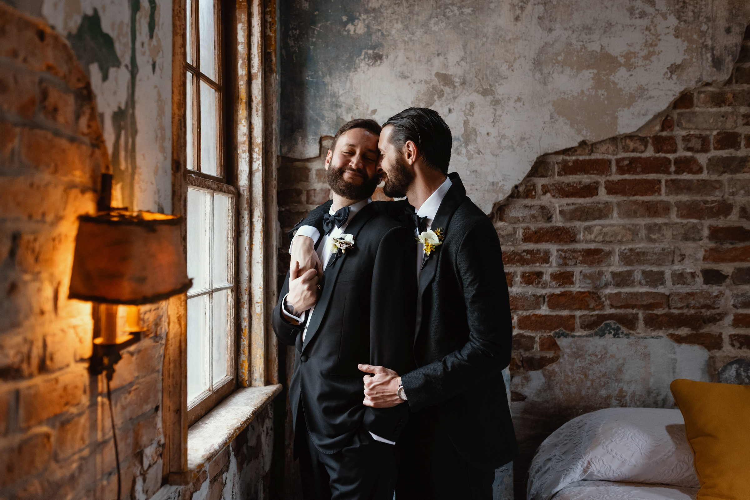 Grooms embracing in distressed style setting - photo by Dark Roux