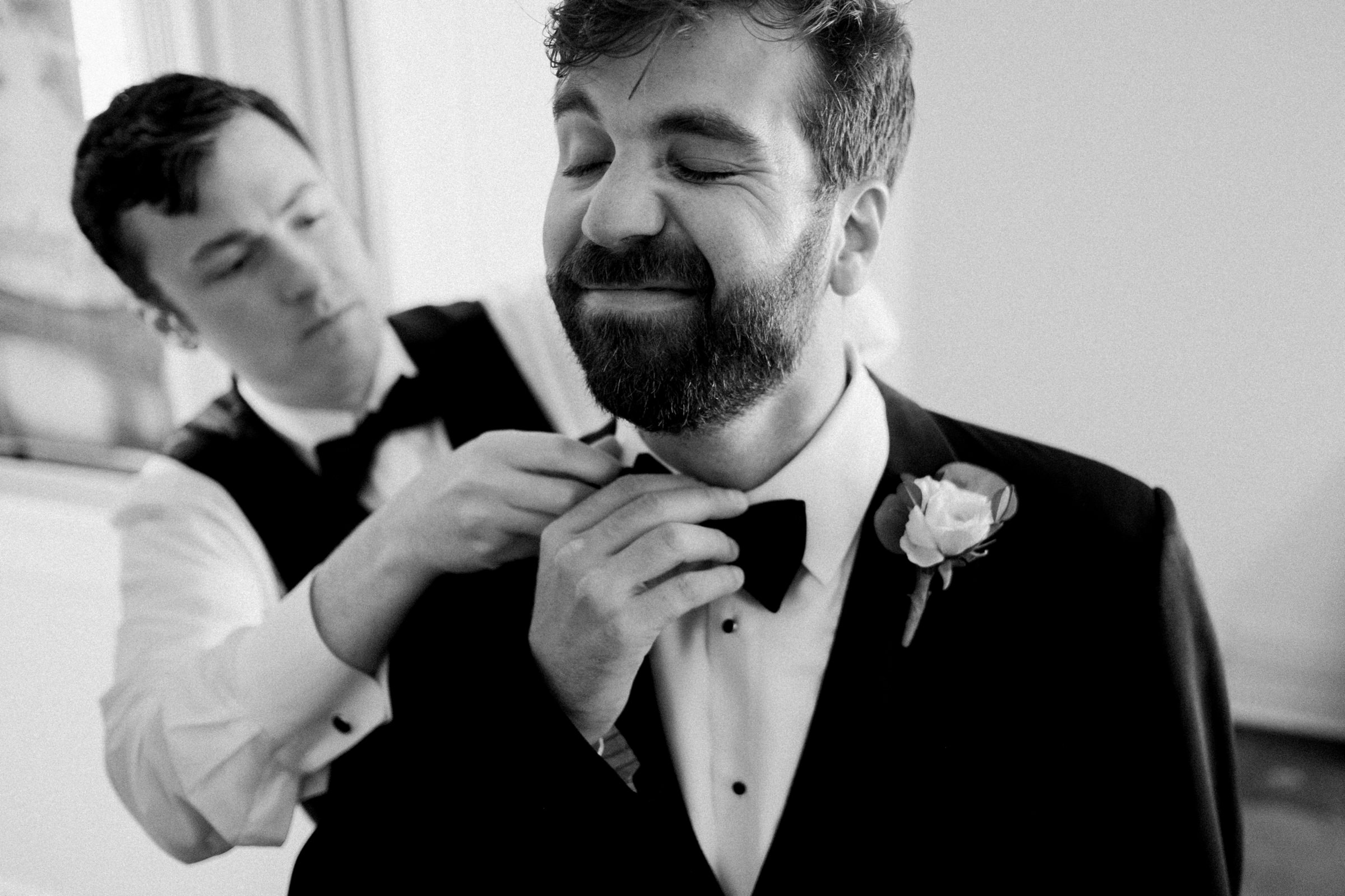 groomsman helping groom with bowtie-new orleans-austin-houston-wedding- photo by Dark Roux