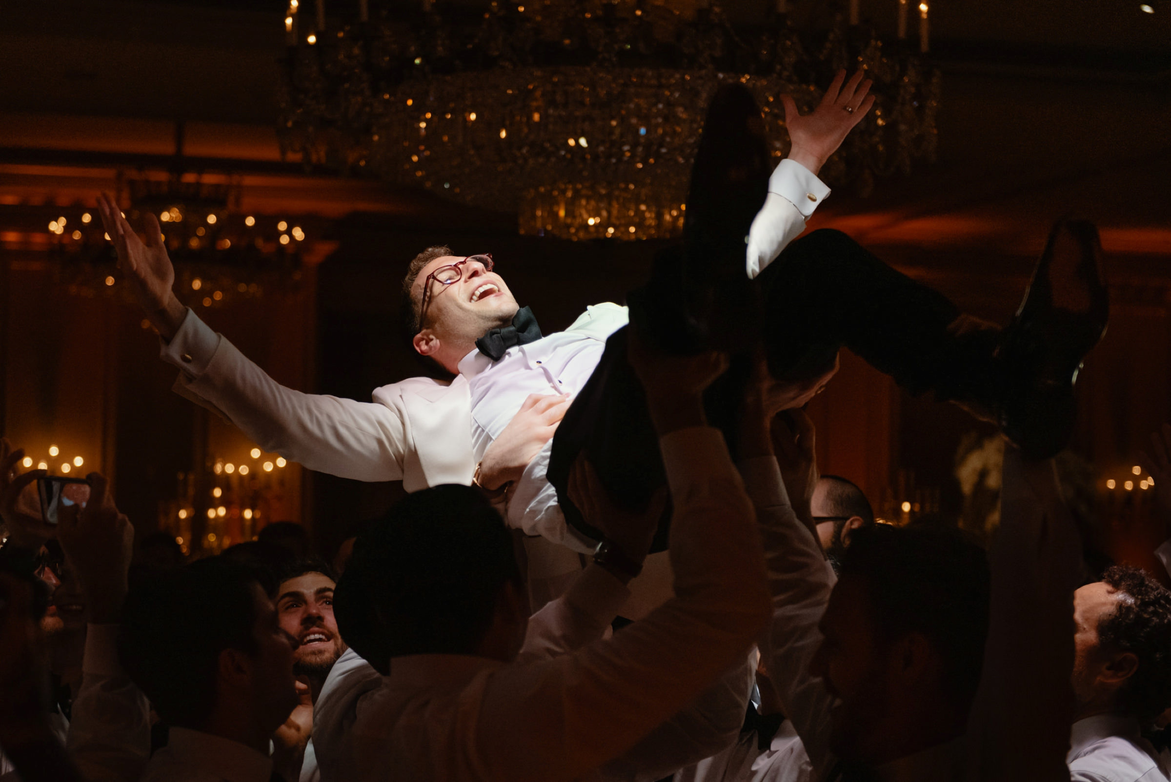 Happy groom held high in the air during reception - photo by Dark Roux