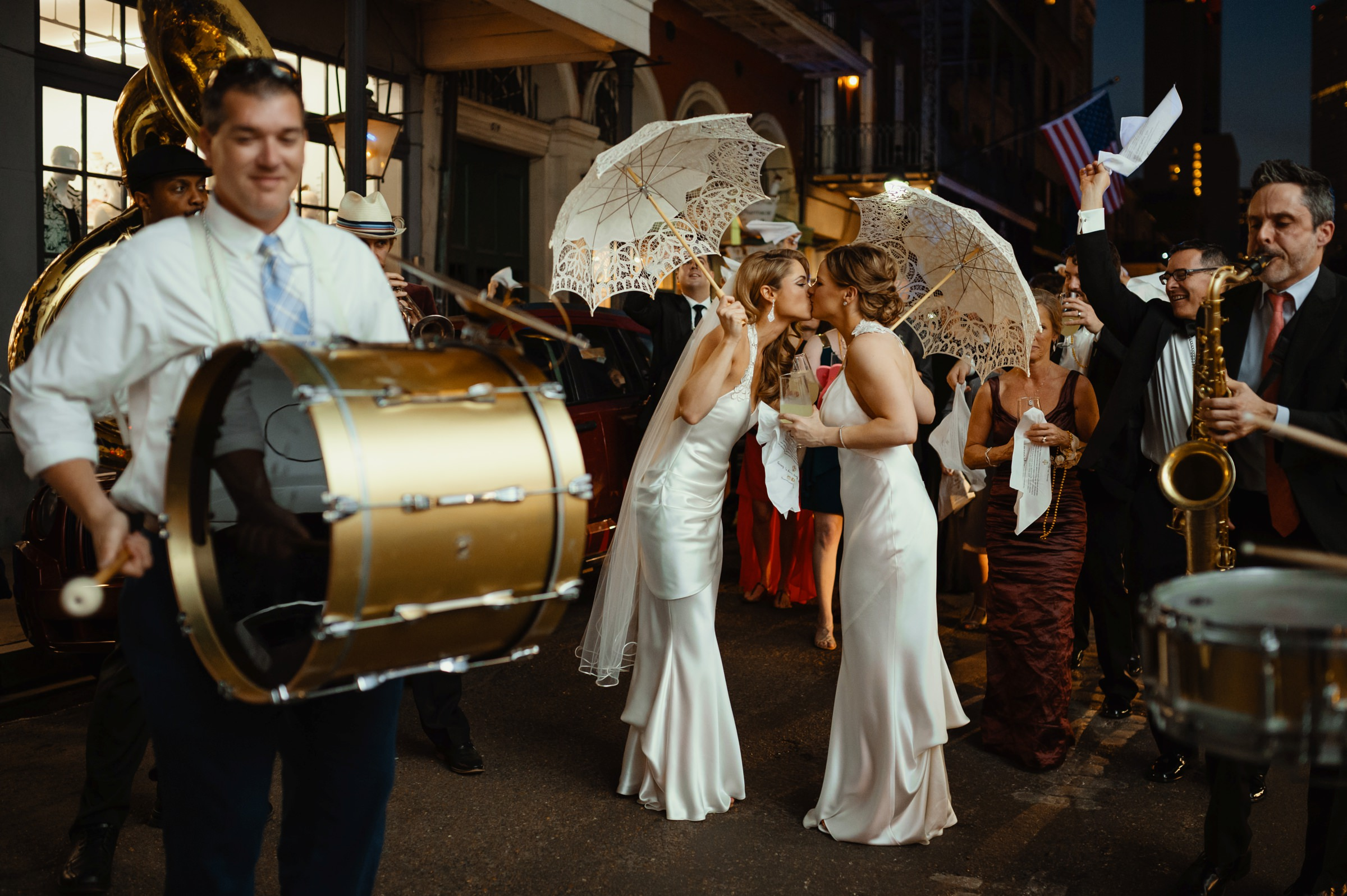 New Orleans two brides kissing amid brass band - photo by Dark Roux