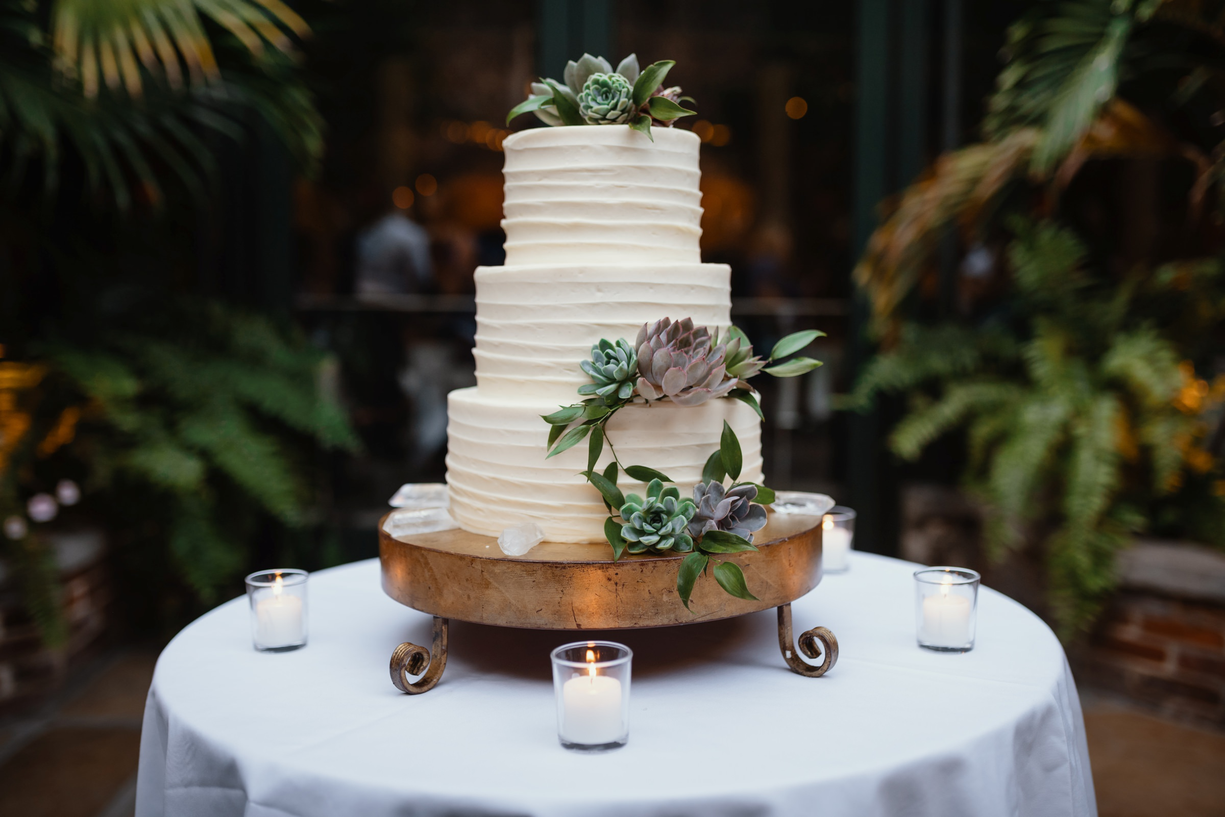 Three tiered cake  on gold platter with succulents and candles - photo by Dark Roux