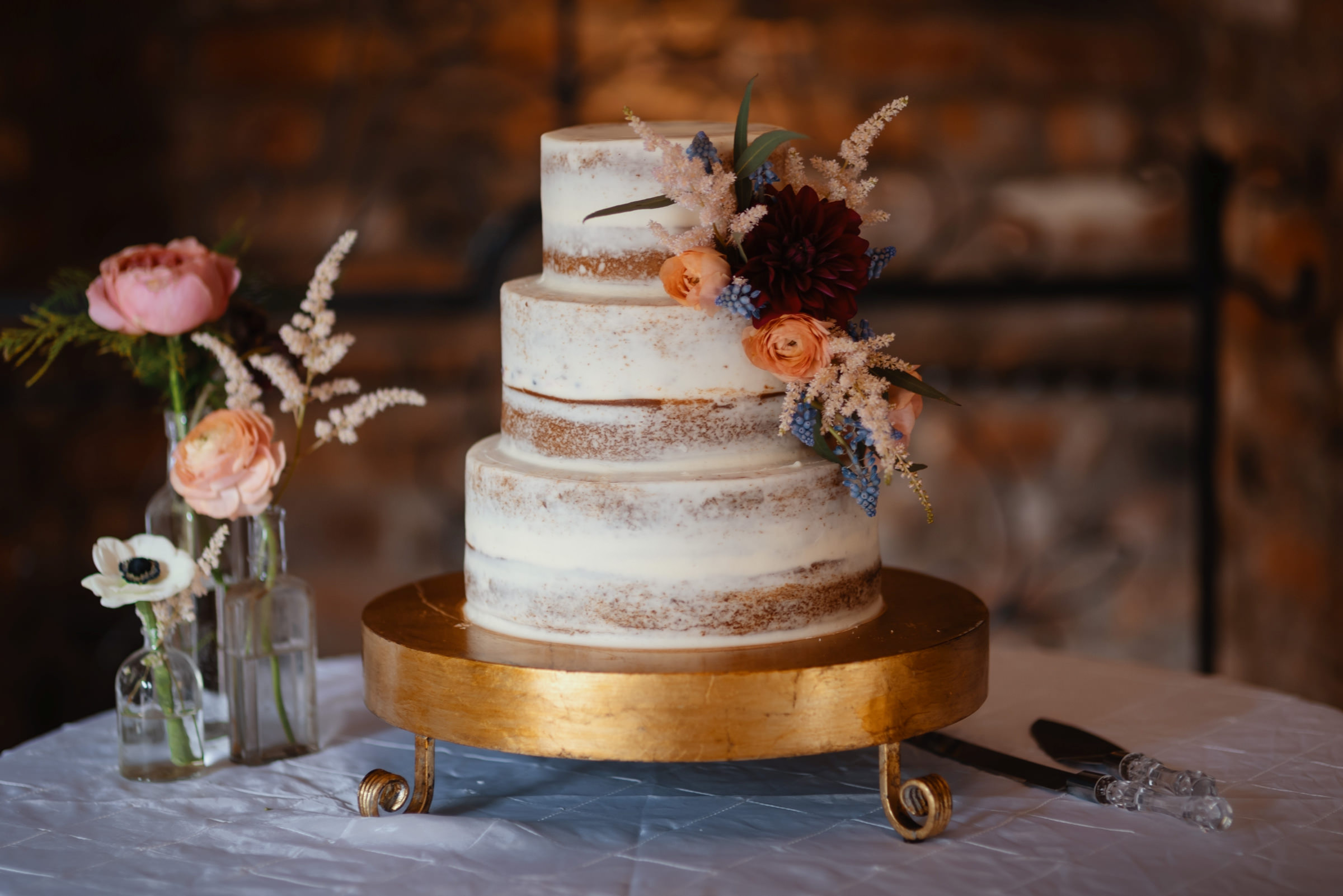 Three tiered cake on gold stand with flowers - photo by Dark Roux