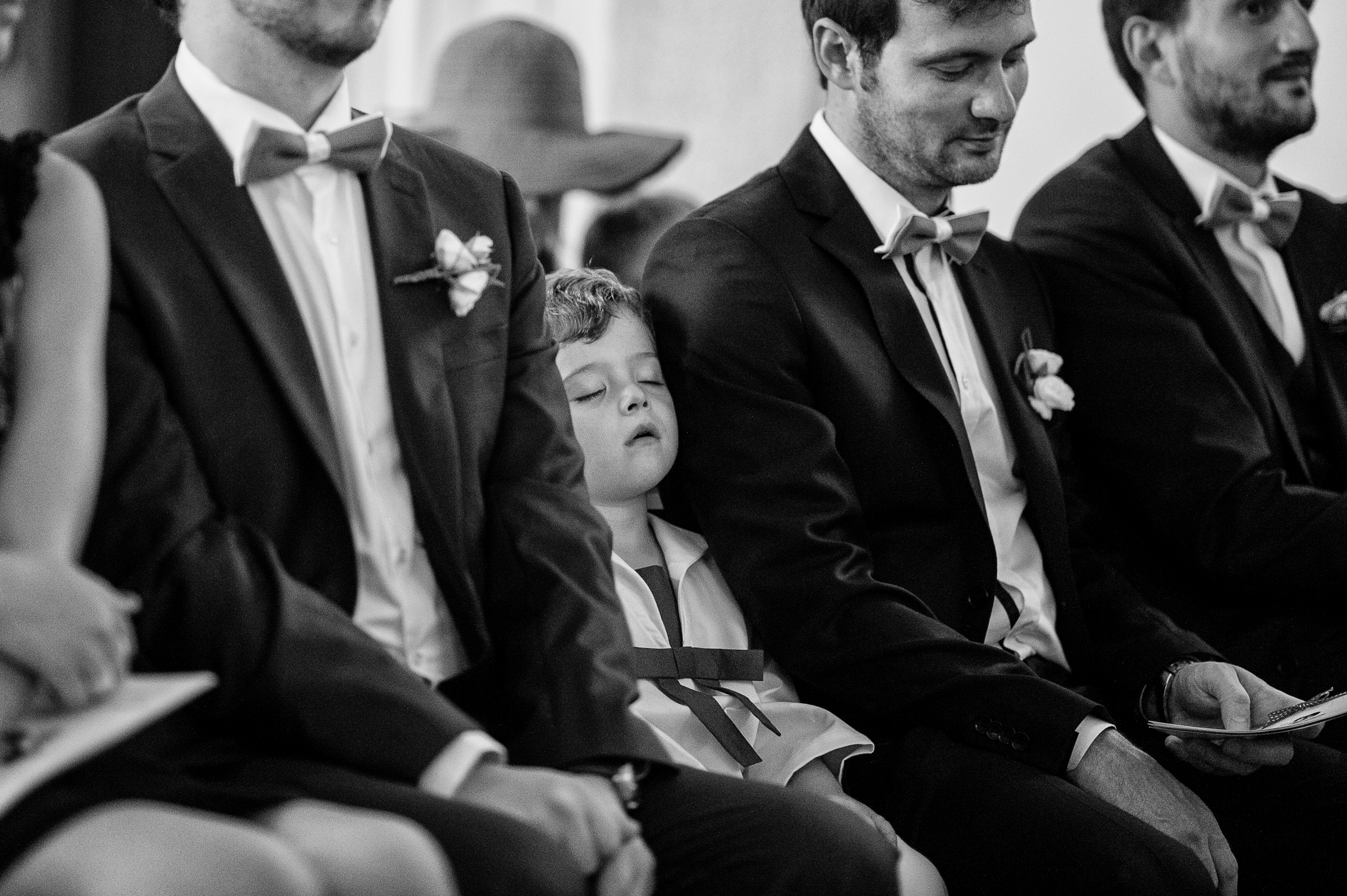 boy napping among seated groomsmen - photo by Gaelle Le Berre Photography
