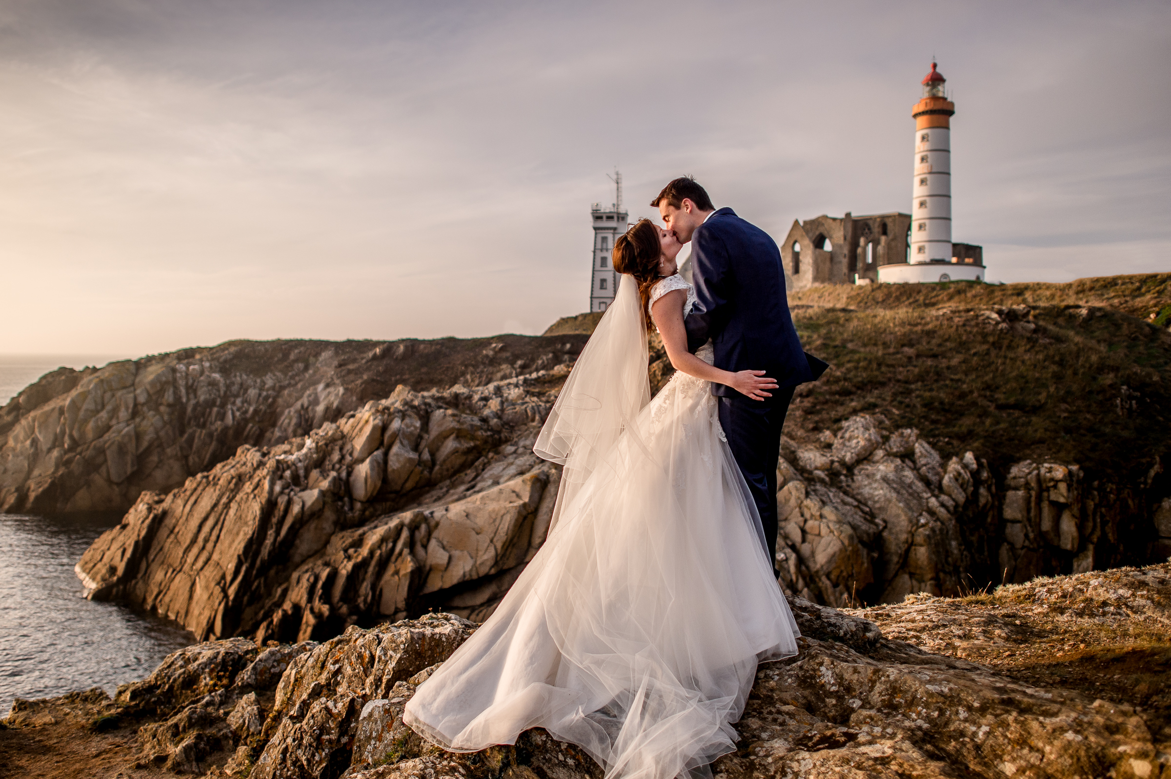Couple kiss on rocky shore against lighthouse - photo by Gaelle Le Berre Photography