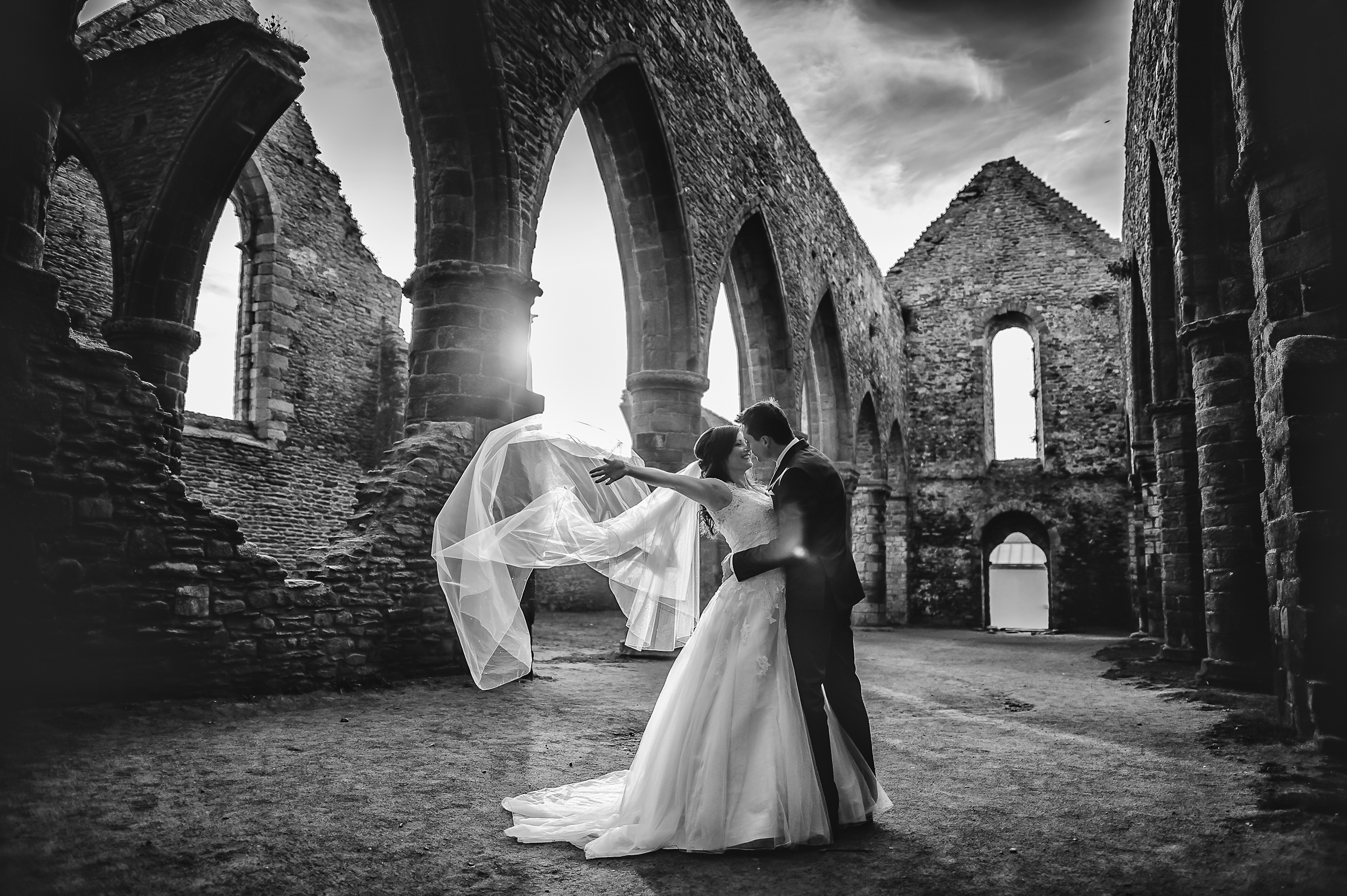 Enthusiastic couple kiss in ancient setting - photo by Gaelle Le Berre Photography