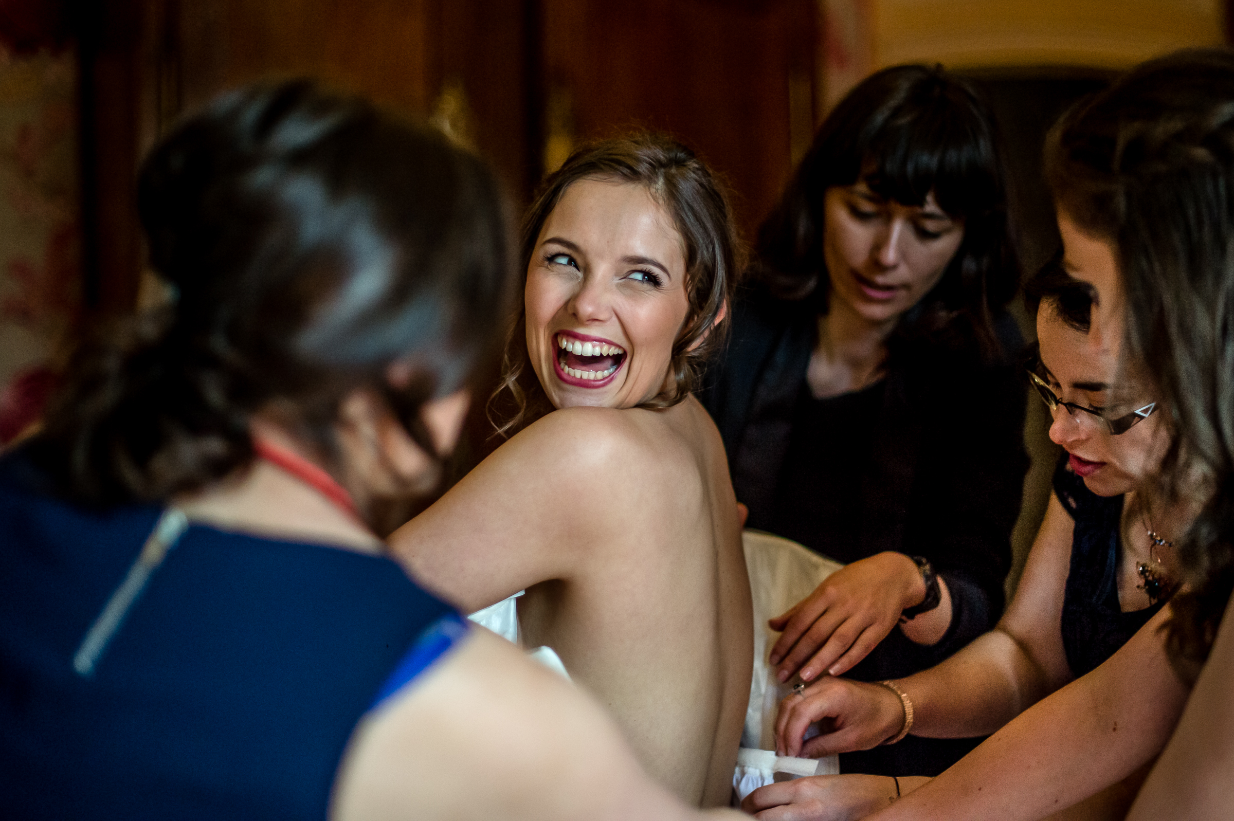 Helping bride into her gown - photo by Gaelle Le Berre Photography