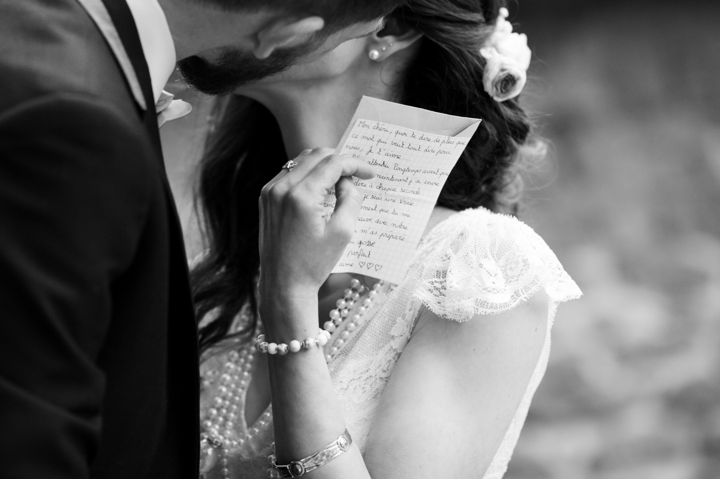 Kiss with bride holding sweet note - photo by Gaelle Le Berre Photography