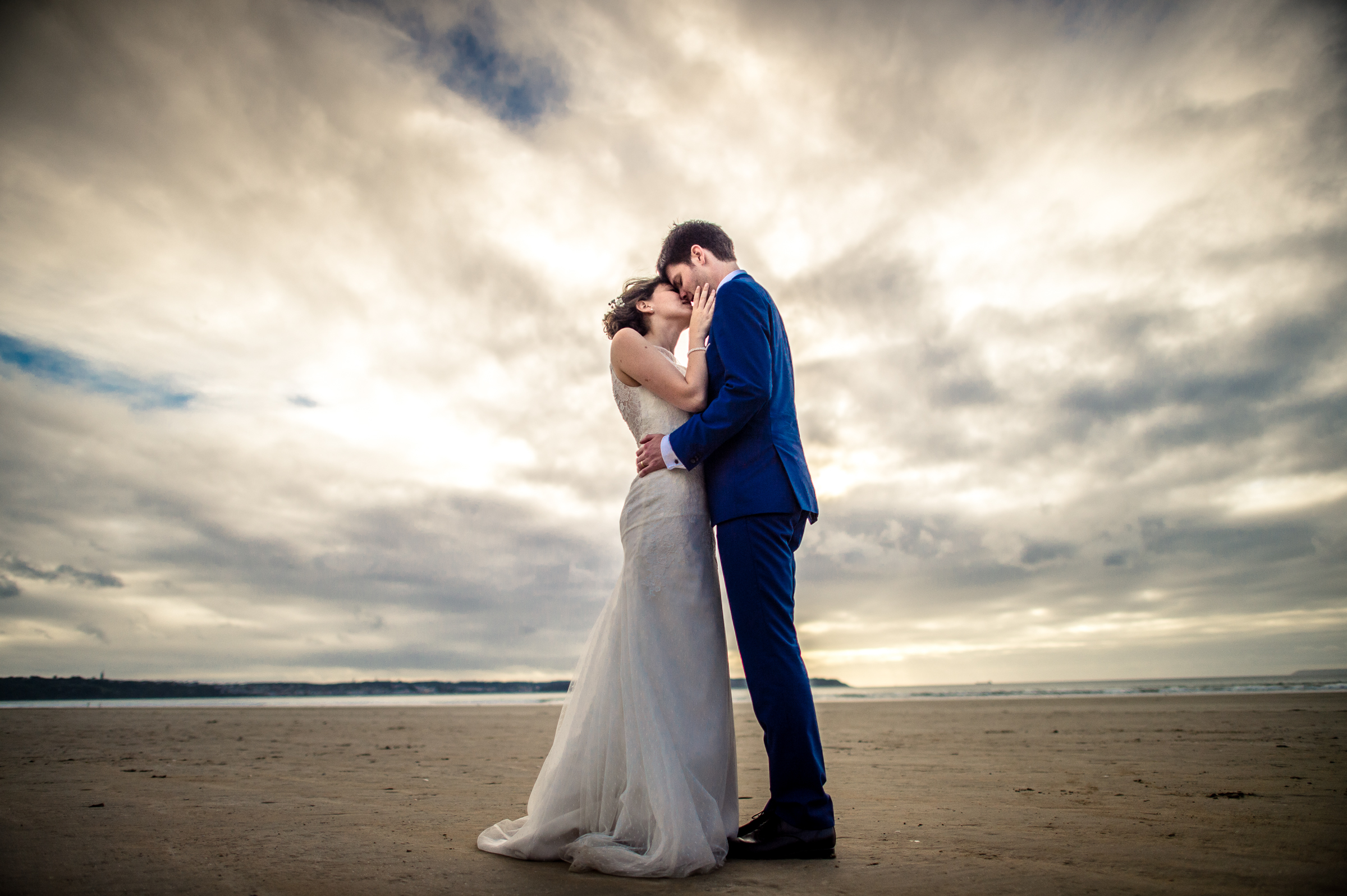 Beachside couple kiss under epic skies - photo by Gaelle Le Berre Photography