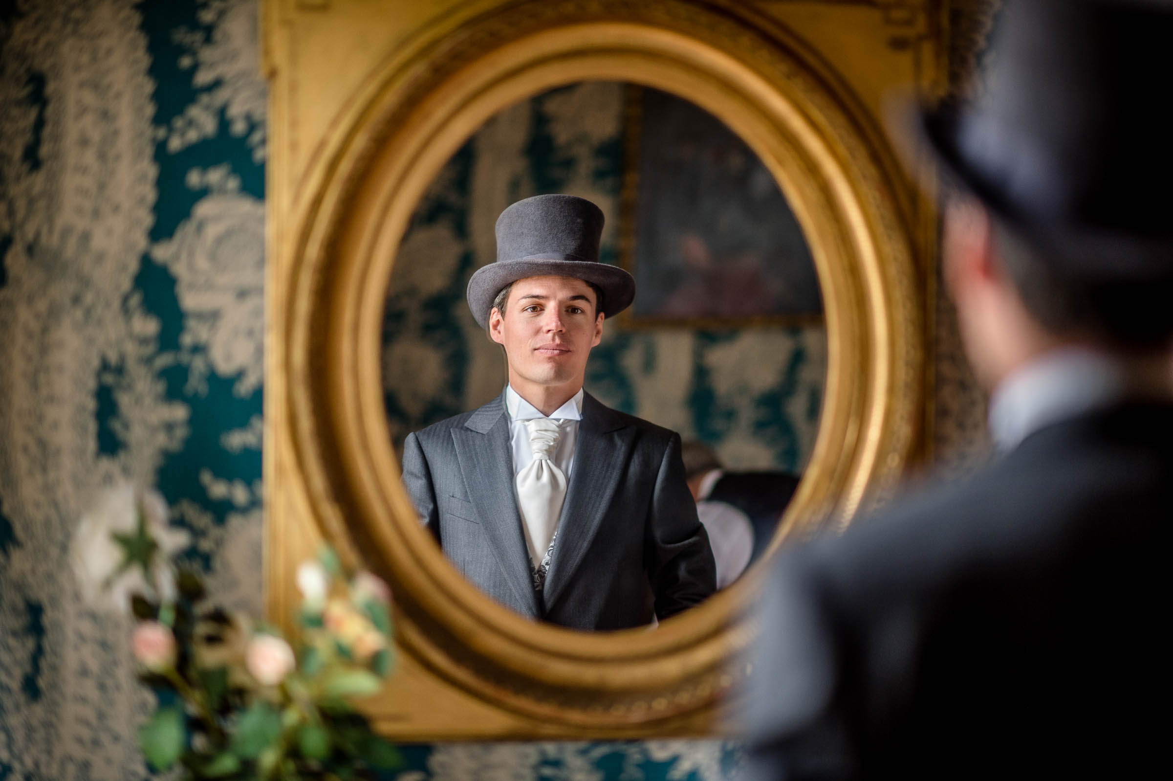 Reflection of groom in grey top hat and suit - photo by Gaelle Le Berre Photography