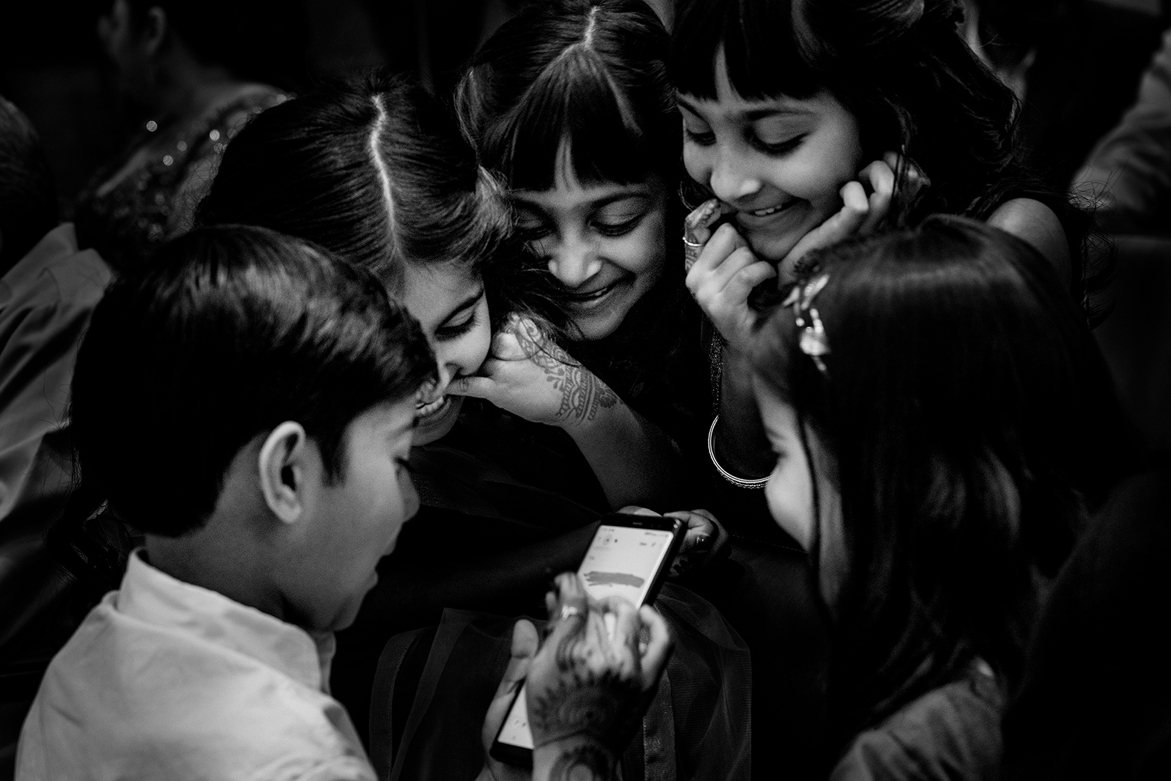 Children gather around phone - photo by Matei Horvath Photography