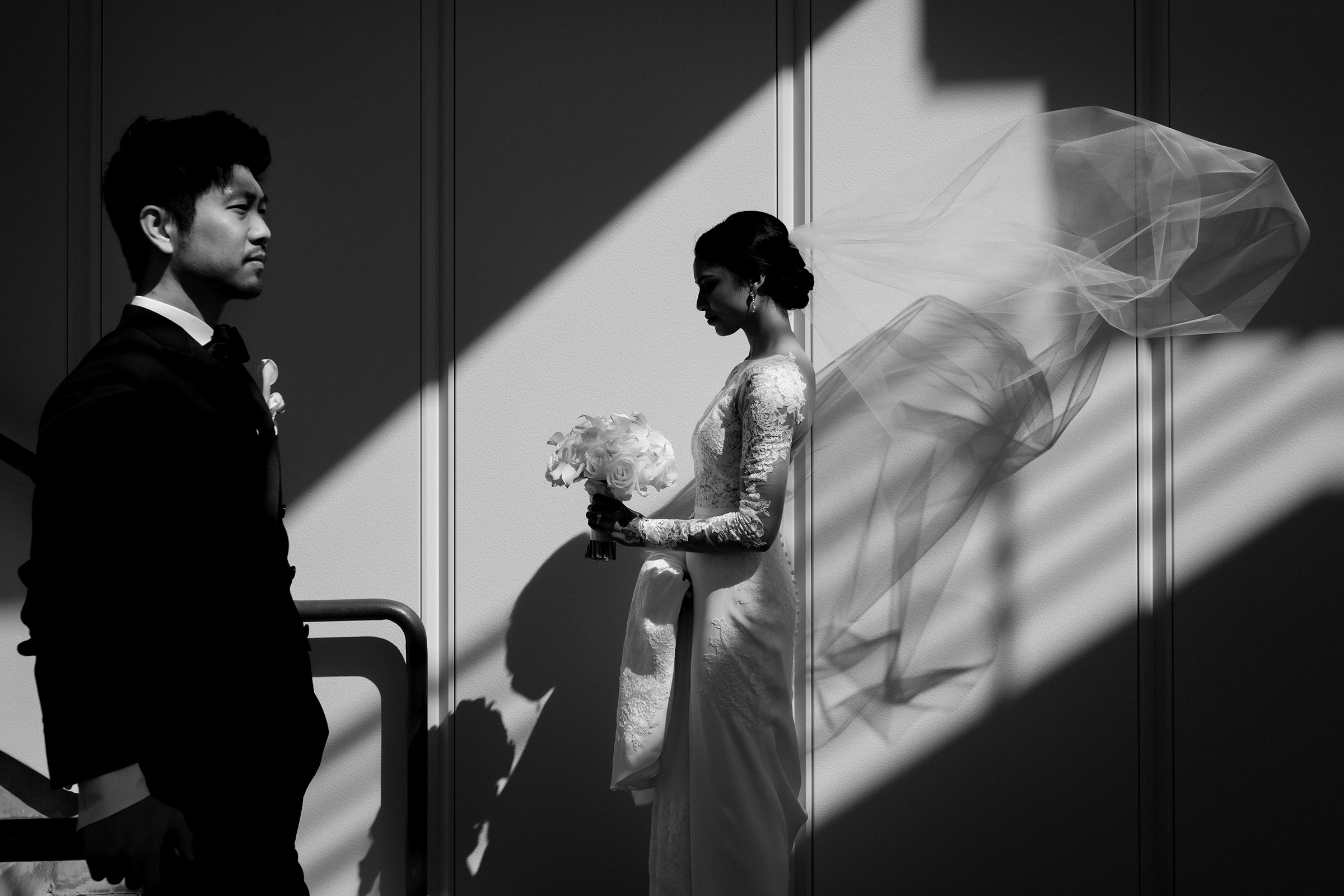 Couple profile pose with veil in breeze and shadows - photo by Matei Horvath Photography
