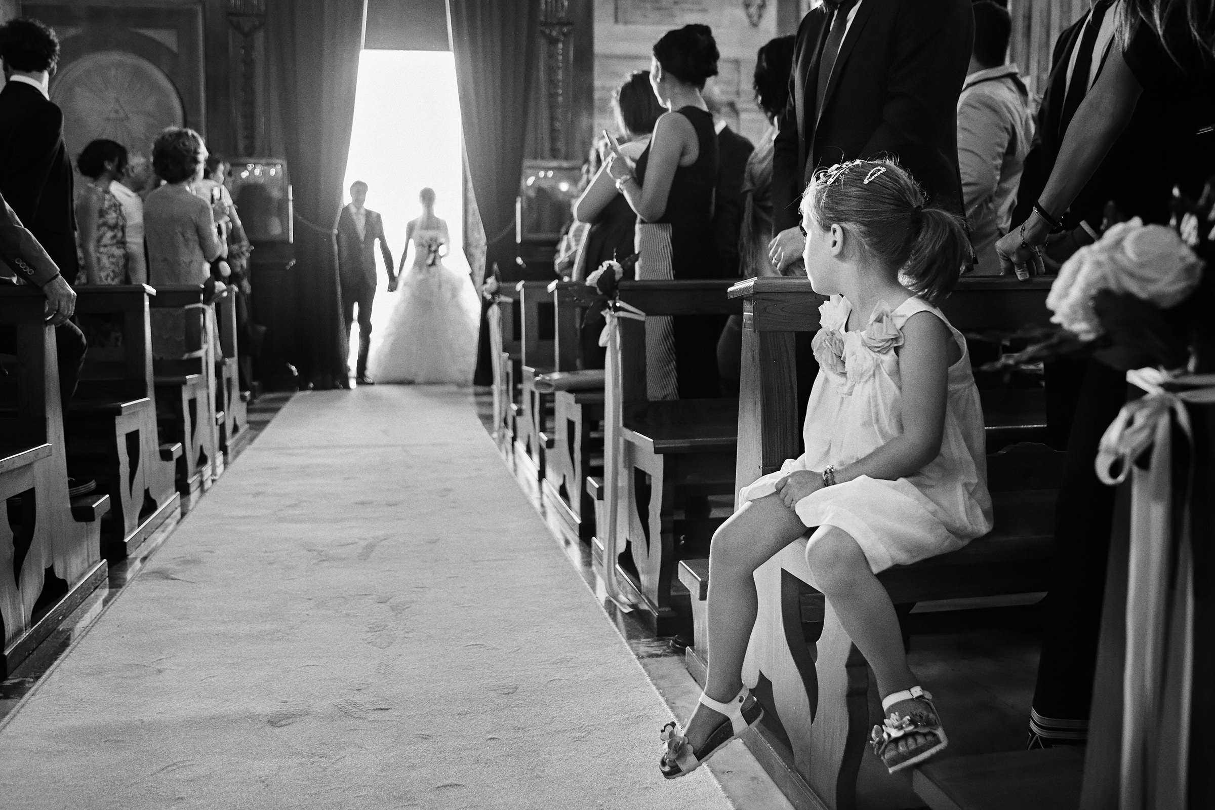 Bride and father appear in church entrance - photo by Andrea Bagnasco Fotografie