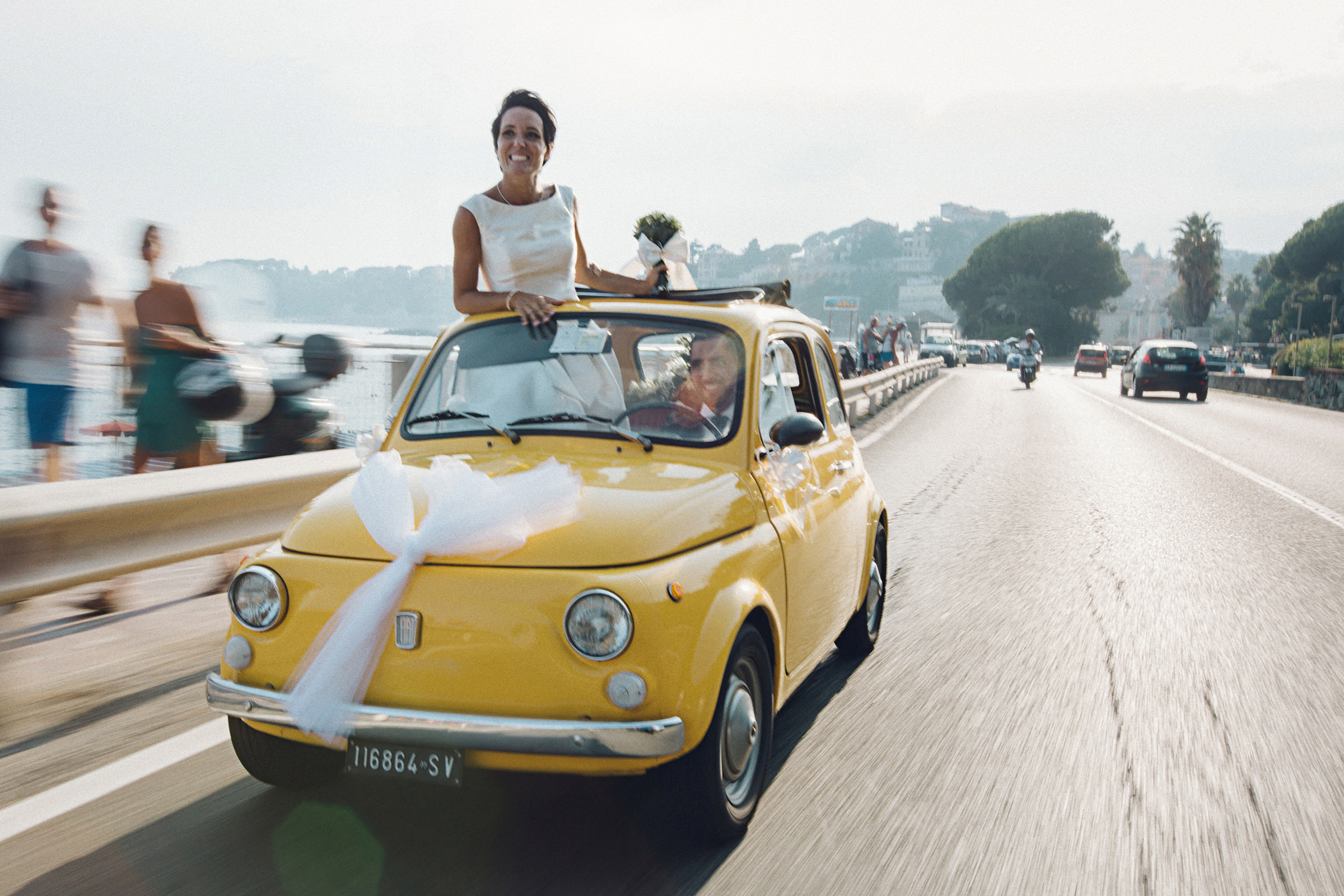 Bride standing in little yellow car as couple drives over scenic bridge  - photo by Andrea Bagnasco Fotografie