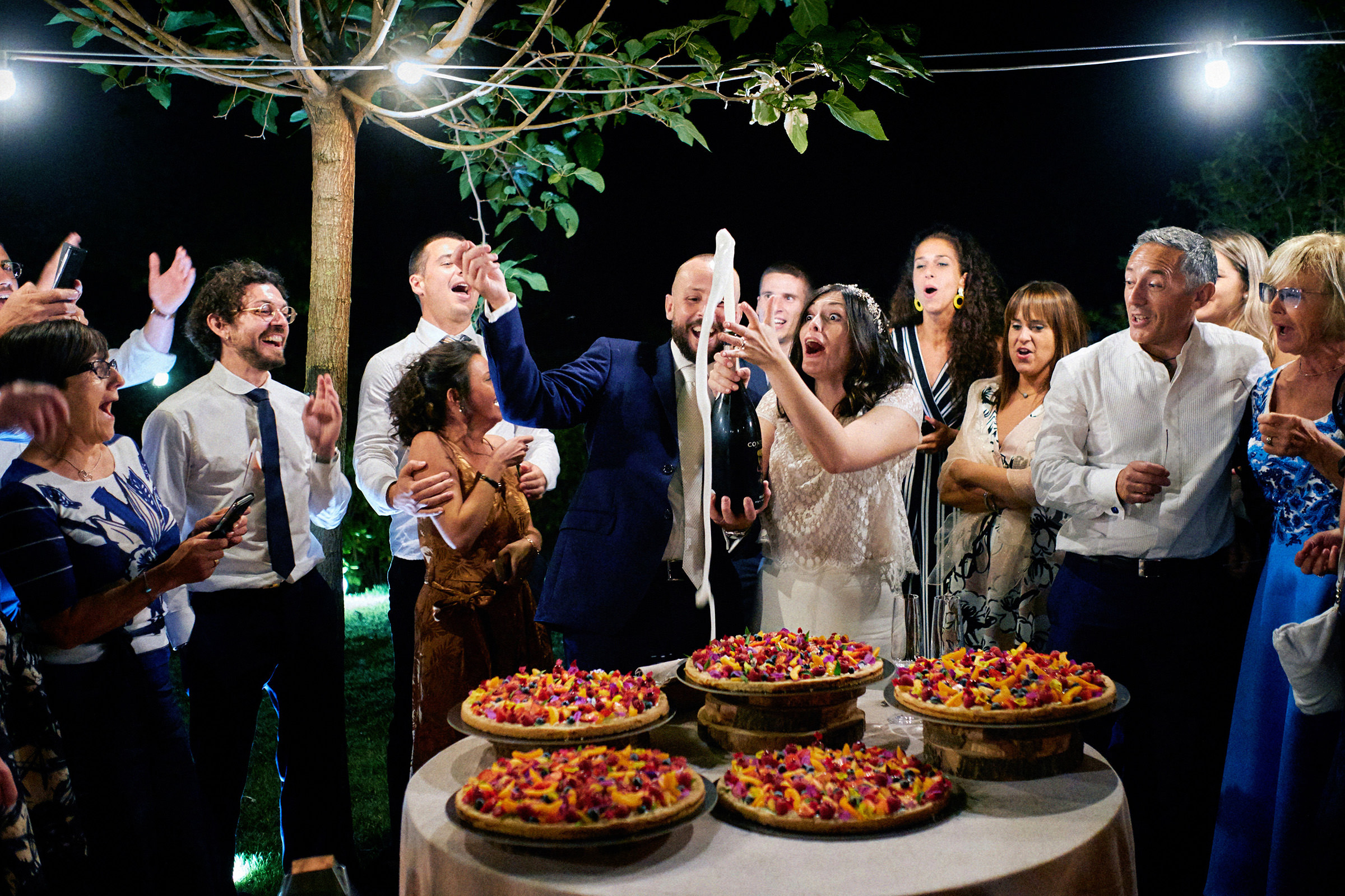 Celebration popping the bubbly amidst happy guests - photo by Andrea Bagnasco Fotografie