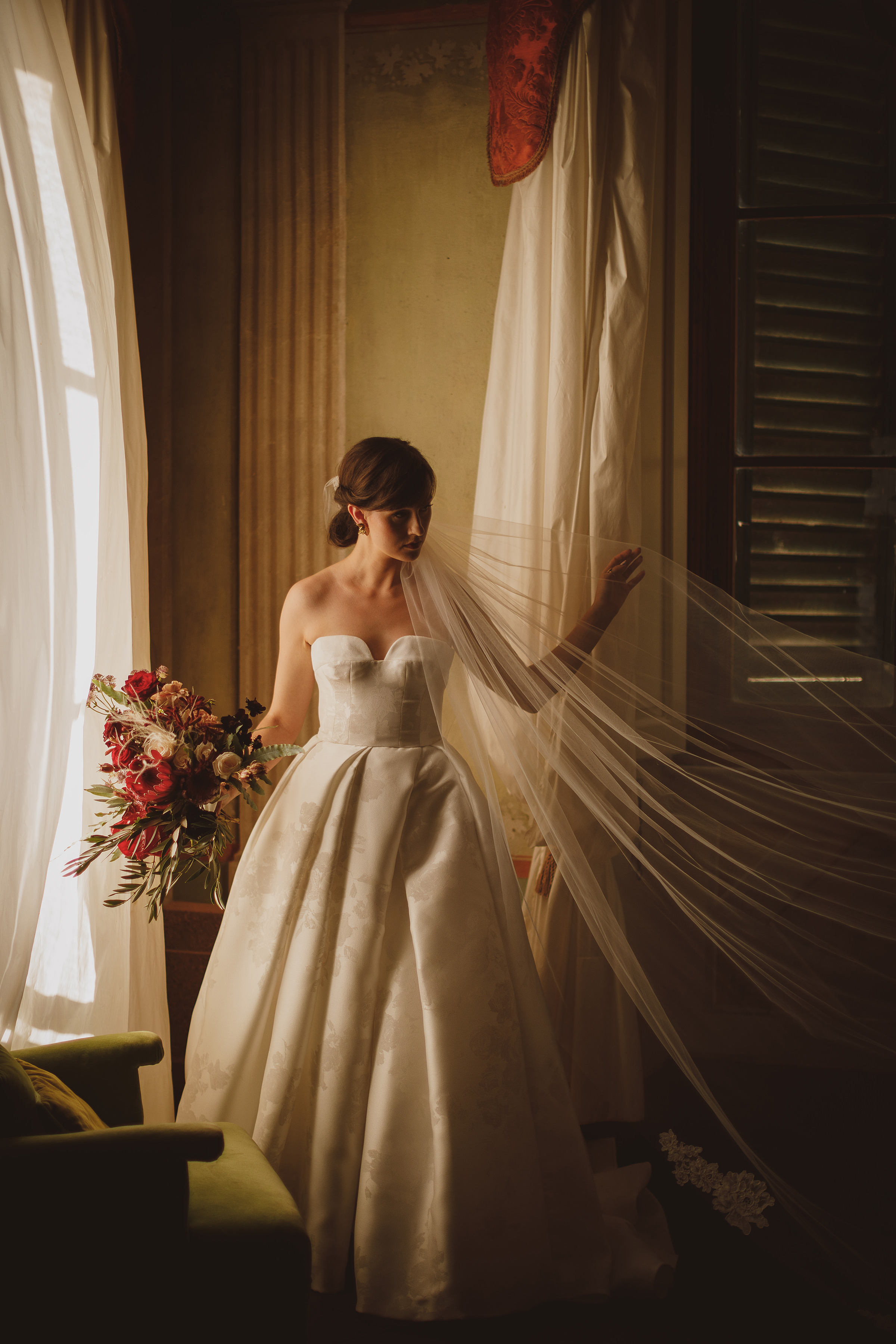 Bride holding bouquet and long veil - photo by Ed Peers Photography