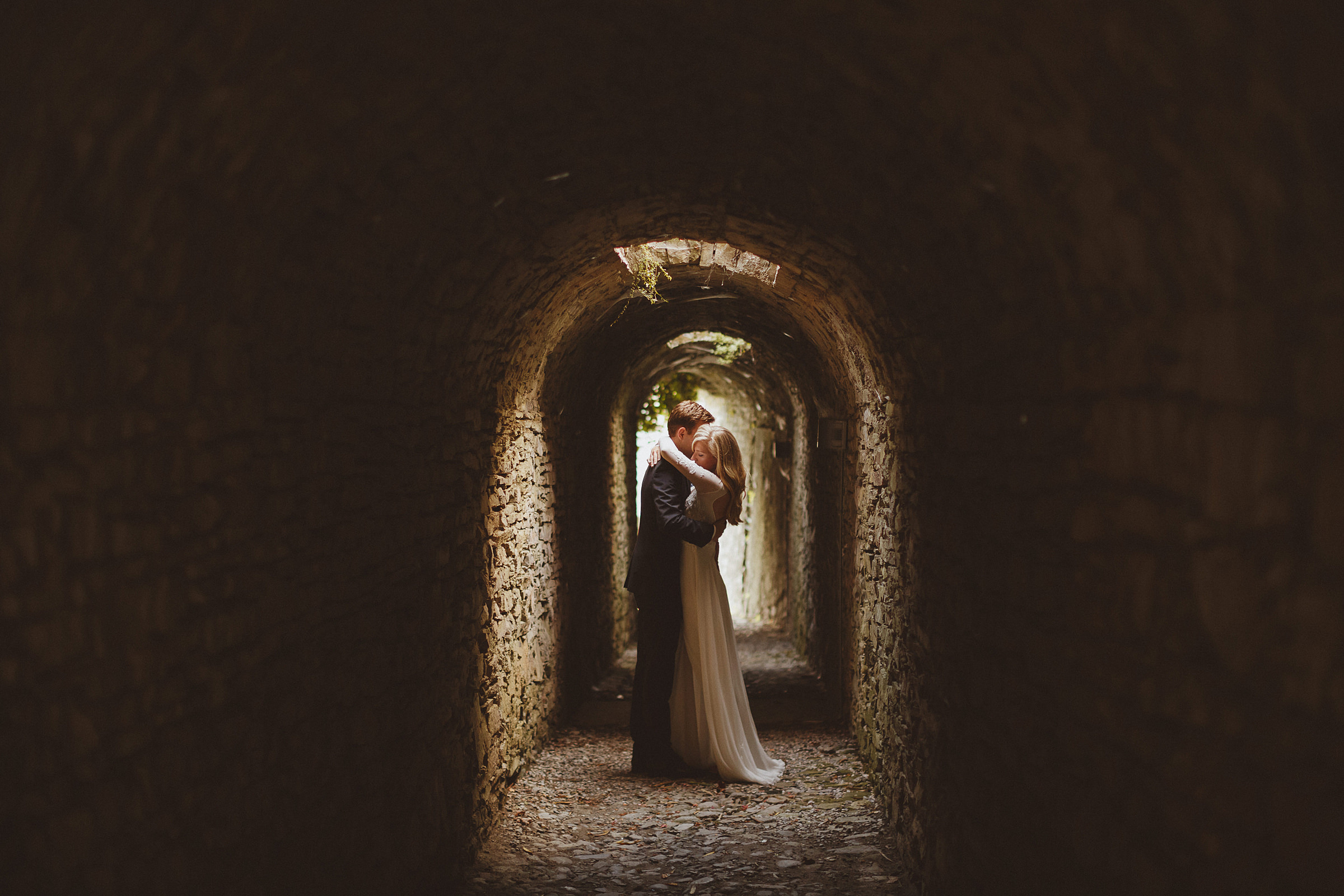 Couple in rustic stone tunnel - photo by Ed Peers Photography