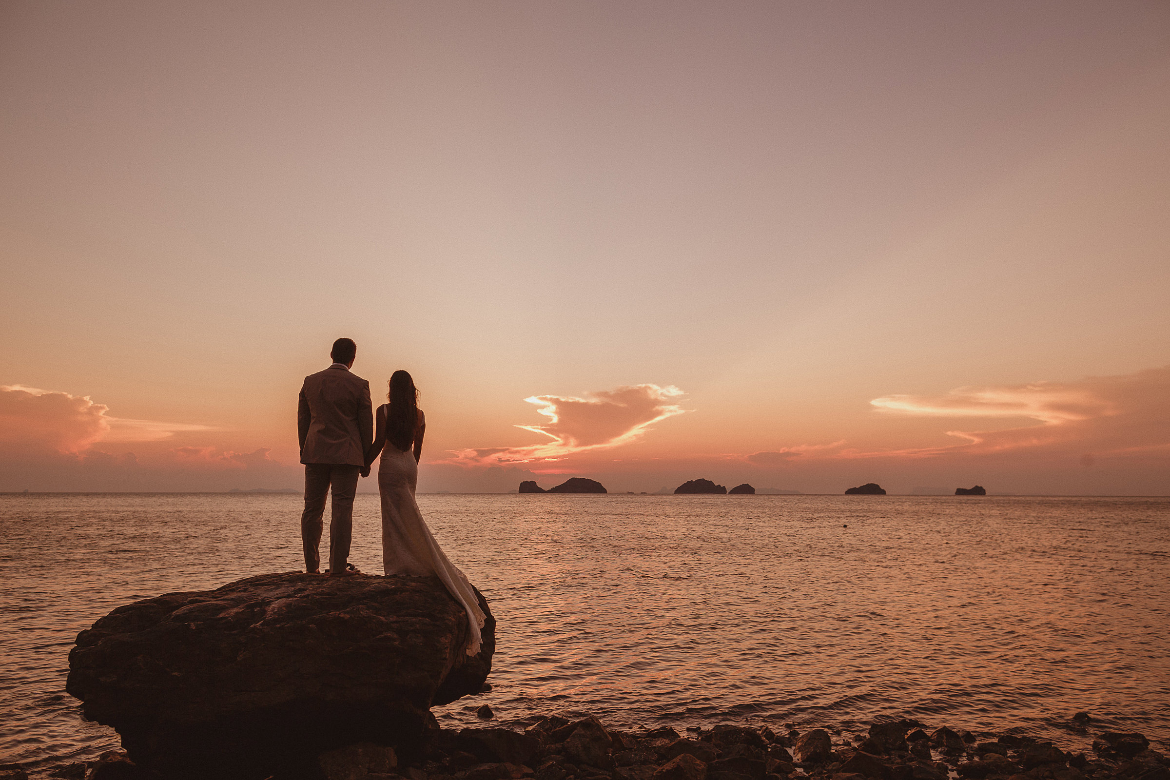 Couple on rock looking out at sunset sea - photo by Ed Peers Photography