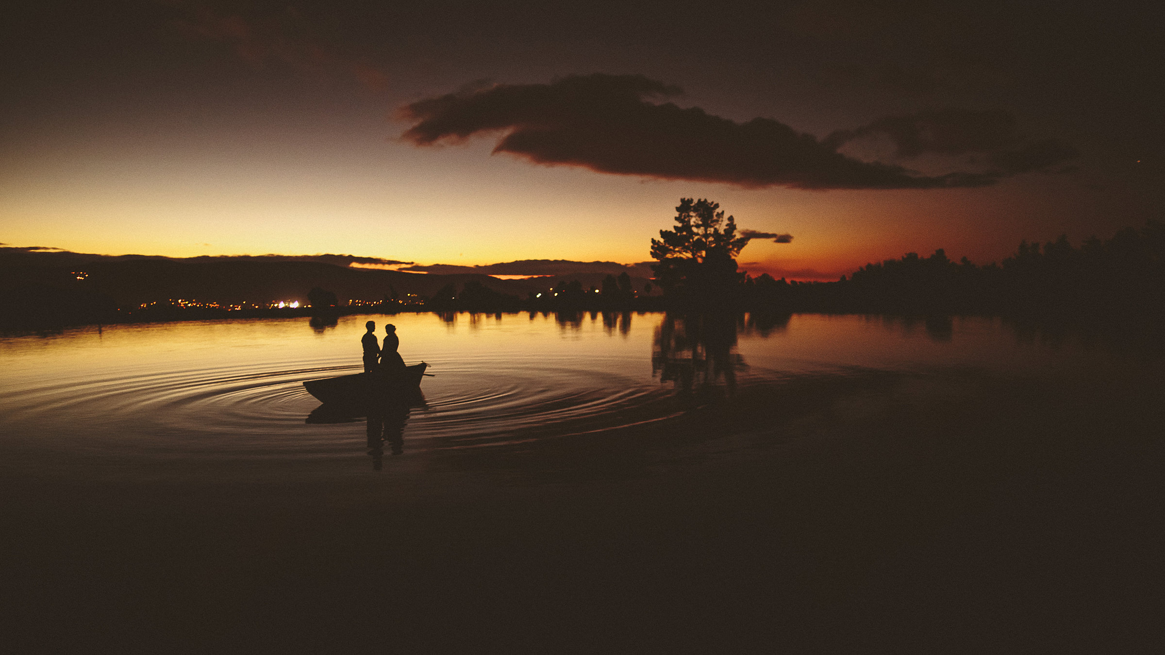 Couple silhouette in small boat at sunset - photo by Ed Peers Photography