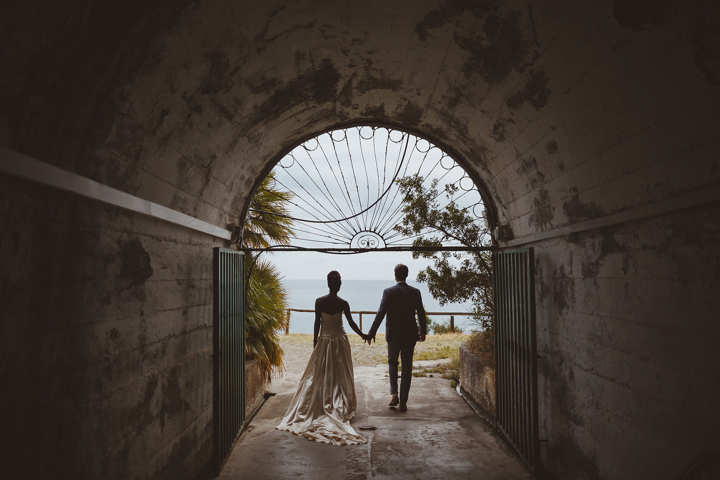 Couple silhouette looking outward from tunnel with ornate grille - photo by Ed Peers Photography