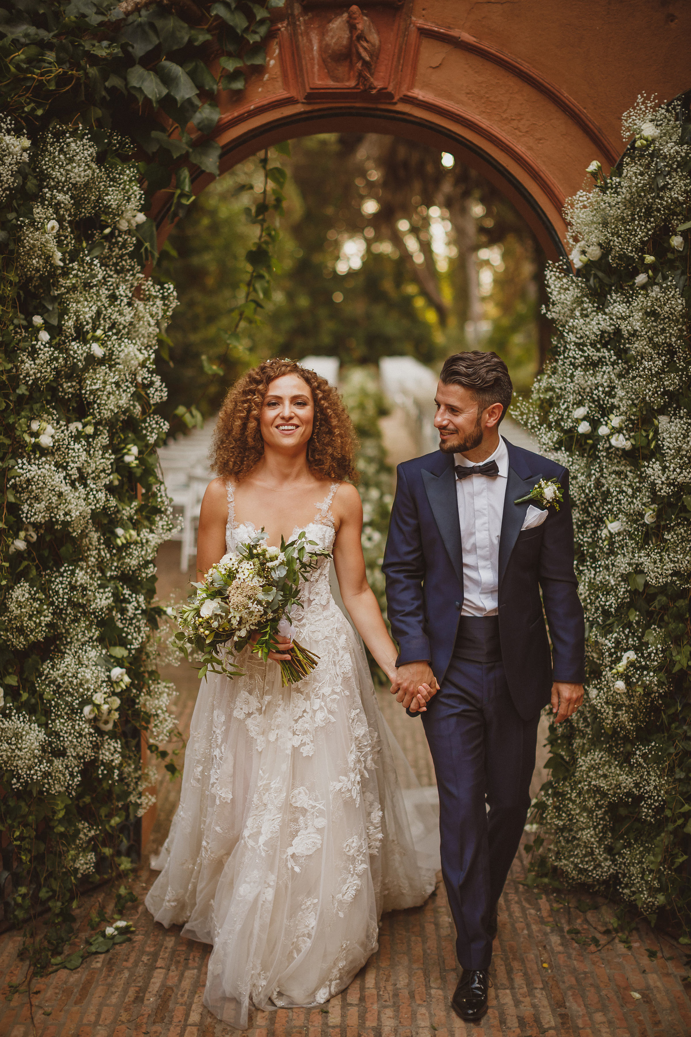 Couple walk through natural floral arbor - photo by Ed Peers Photography