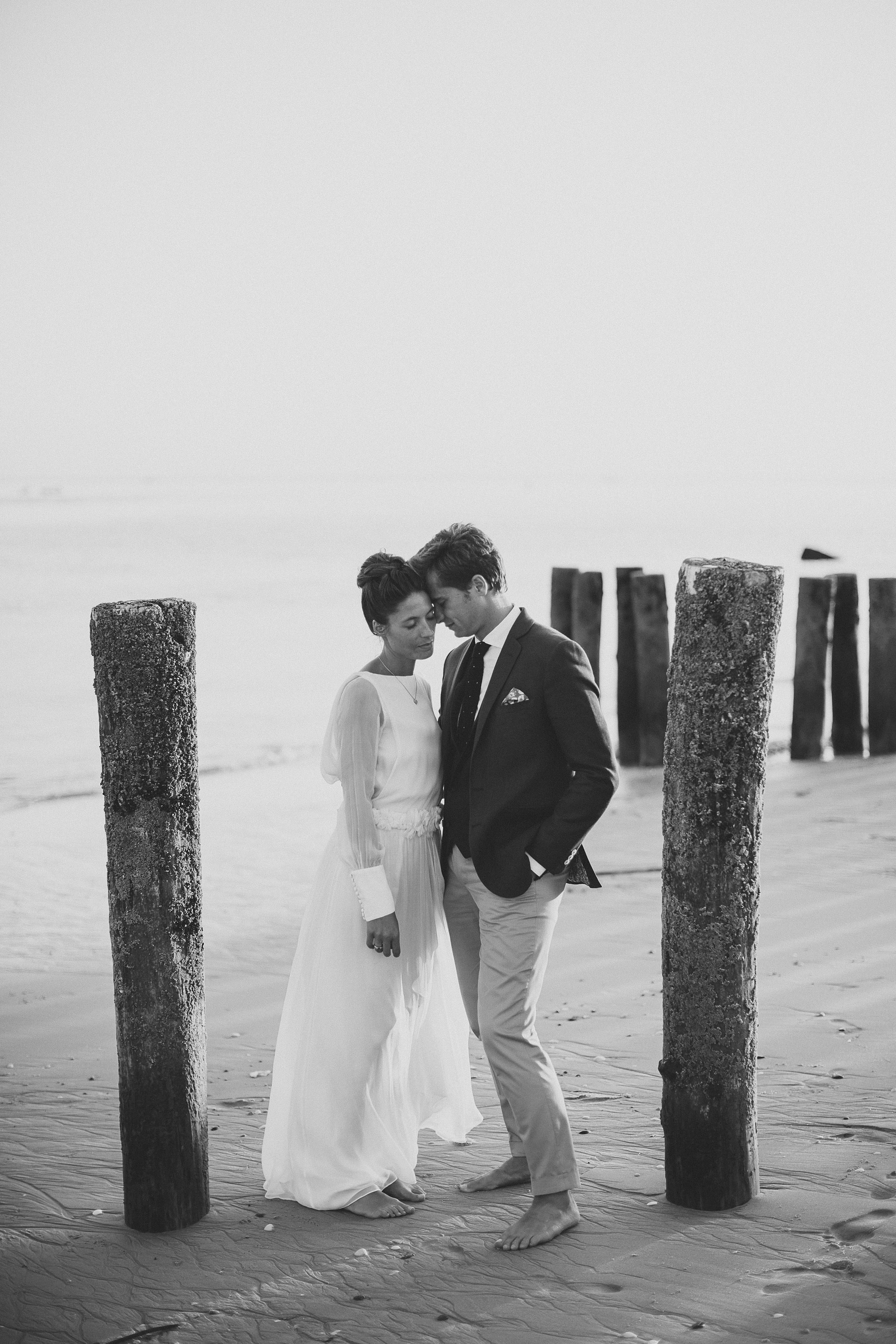 Face to face couple portrait with beach pylons - photo by Ed Peers Photography