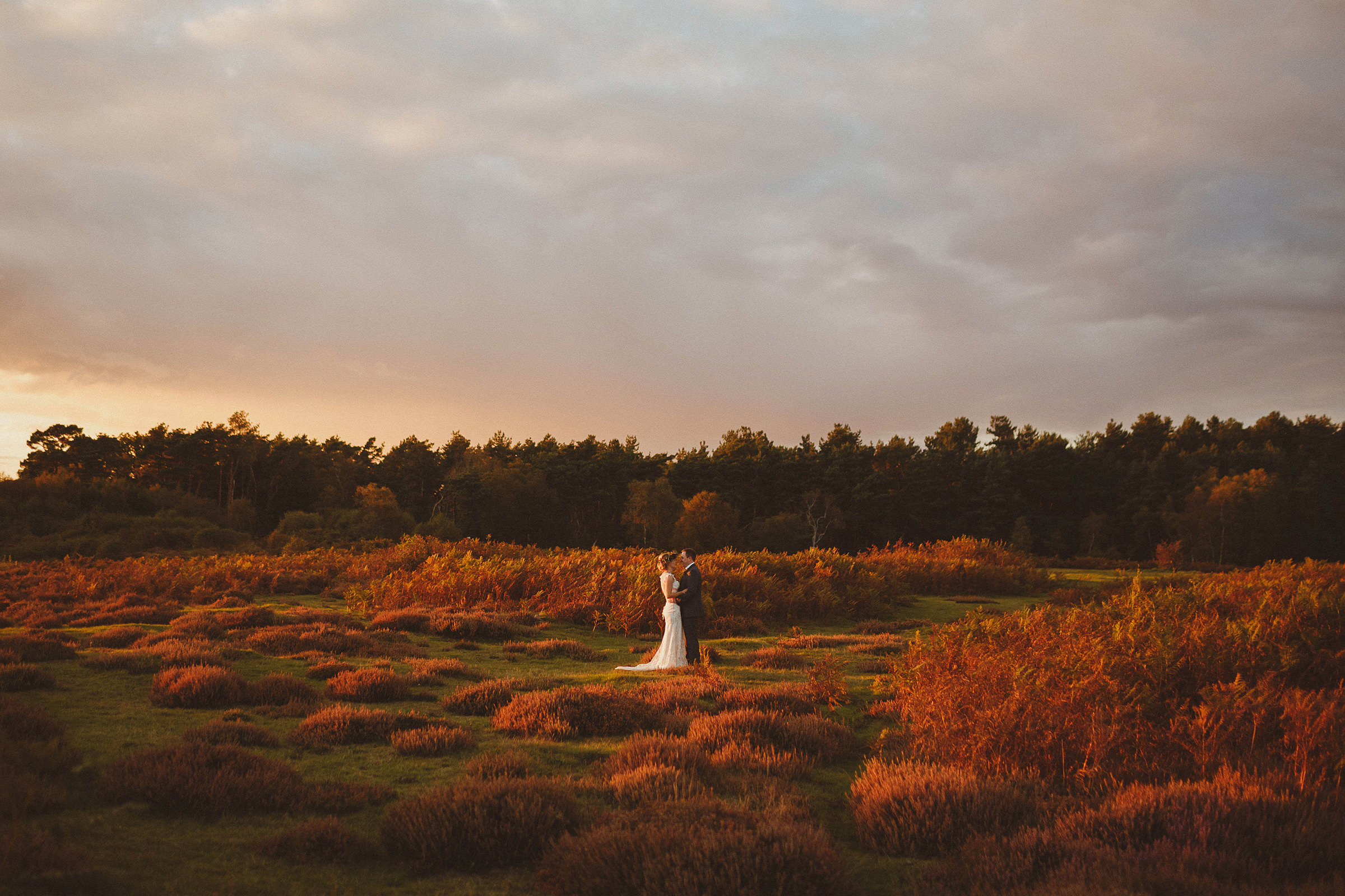 Landscape couple portrait in red and green field - photo by Ed Peers Photography