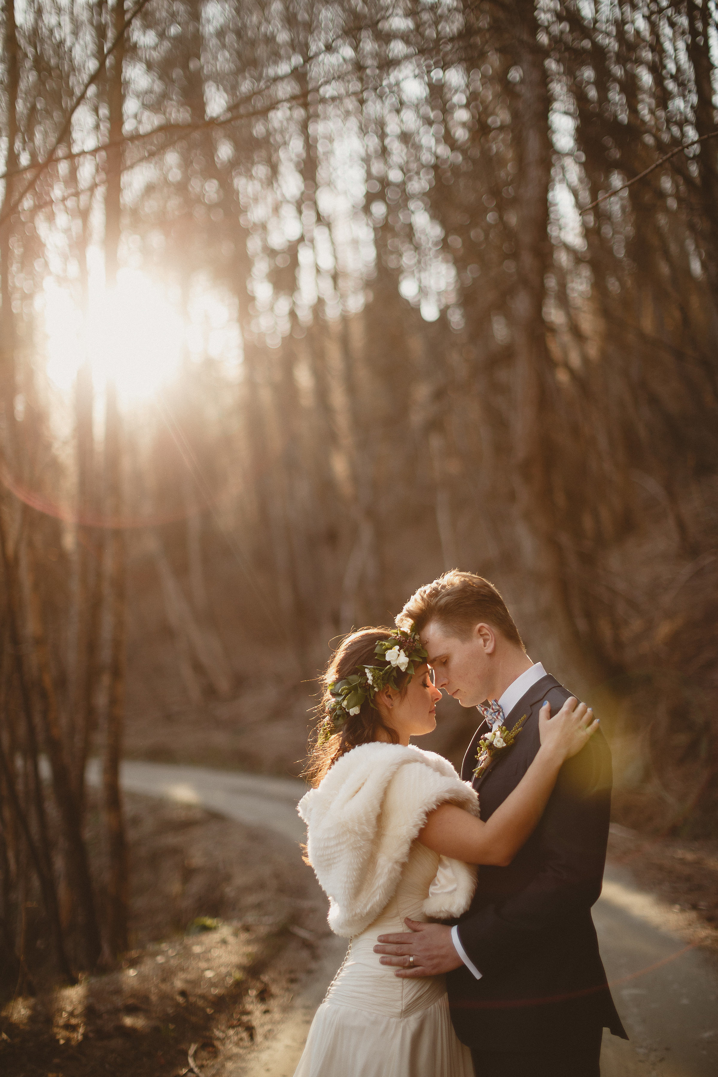 Lens flare couple portrait against trees - photo by Ed Peers Photography