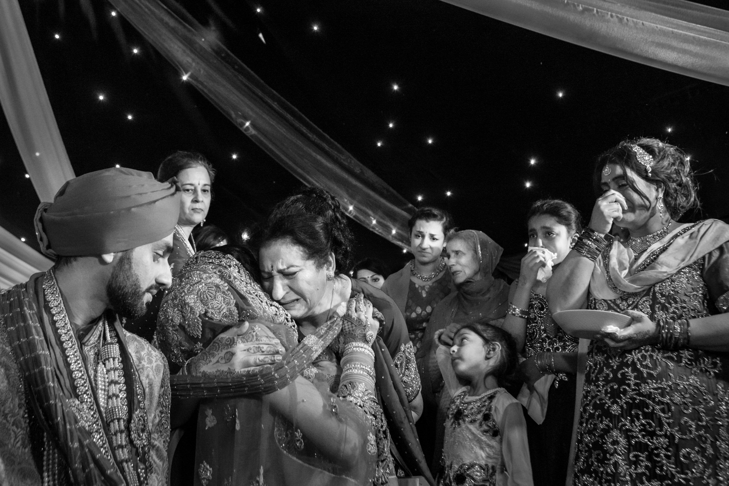 Emotional moment between bride and mother and others - photo by Eye Jogia Photography
