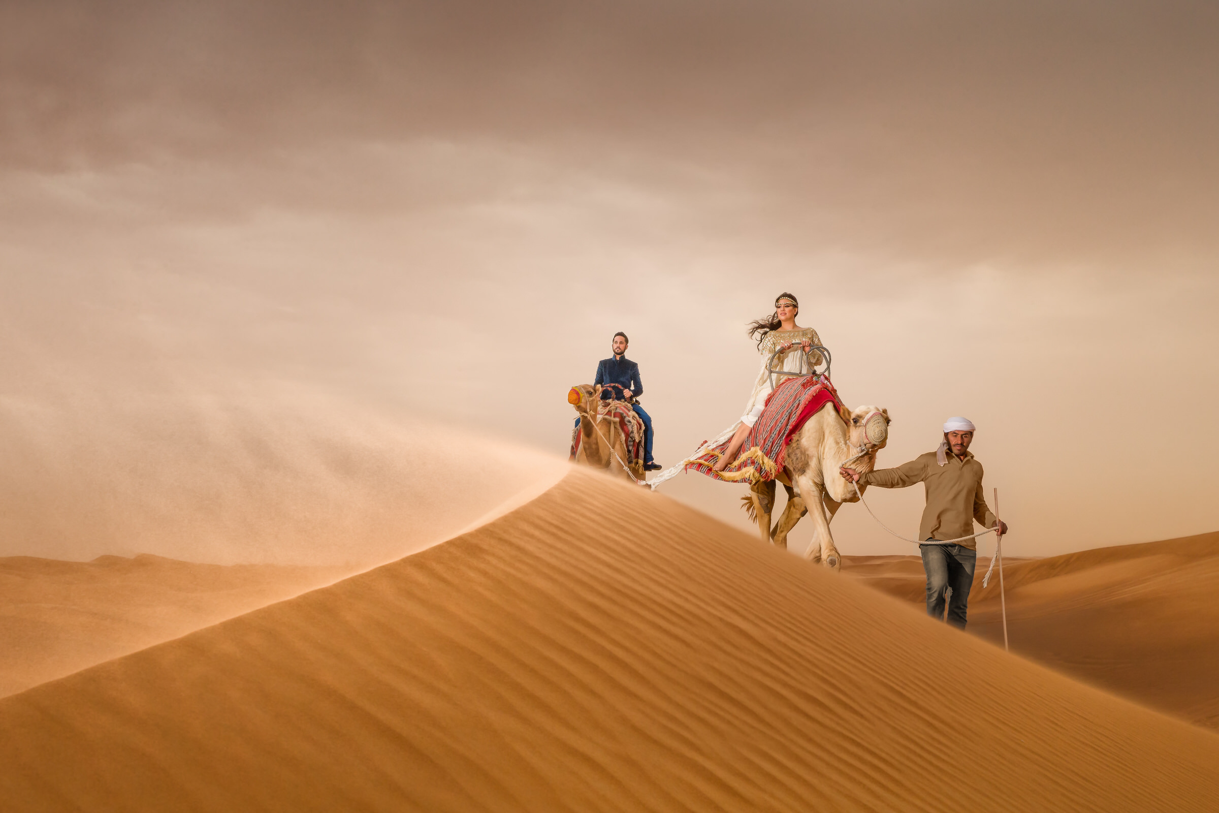 Epic bride and groom portrait on camels on dunes - photo by Eye Jogia Photography