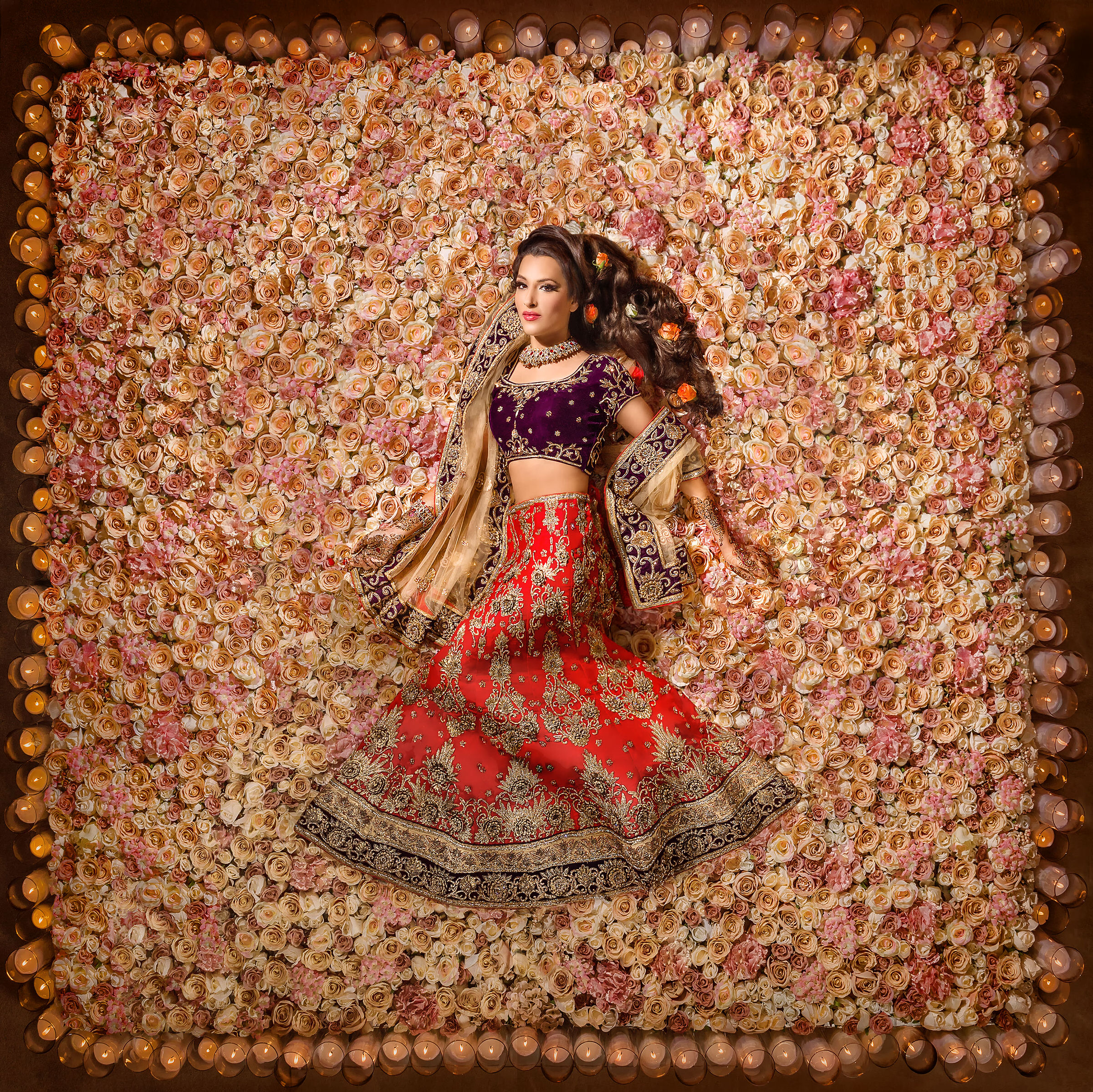 Indian bride against gigantic bed of roses with border of candles - photo by Eye Jogia Photography