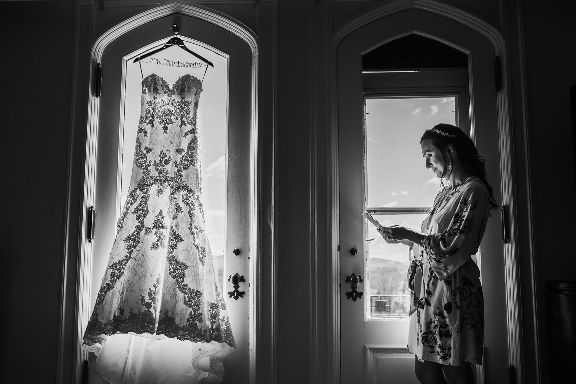 Bride reading letter as gown hangs in window - photo by Kelli Wilke Photography