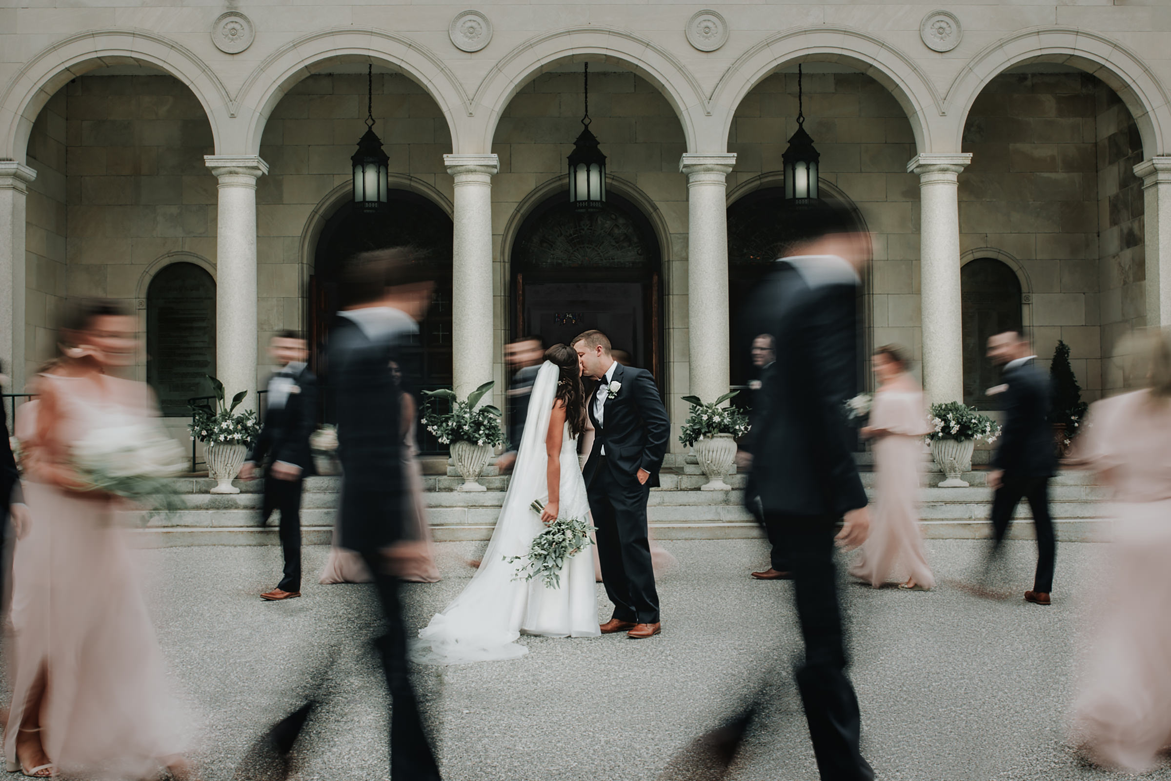 Couple kiss among wedding party at colonnade - photo by Kelli Wilke Photography