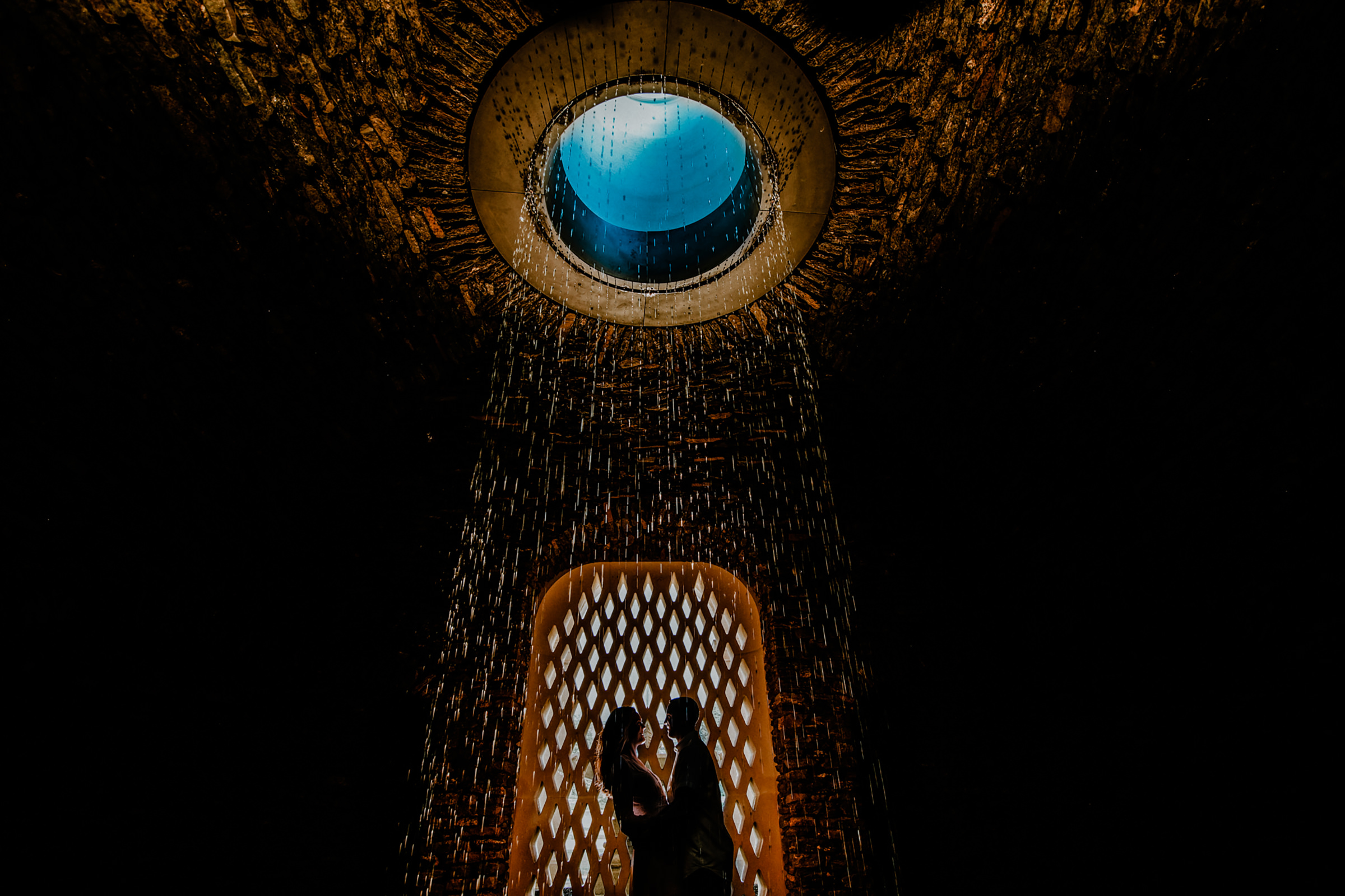 Silhouette couple under circular fountain - photo by Kelli Wilke Photography