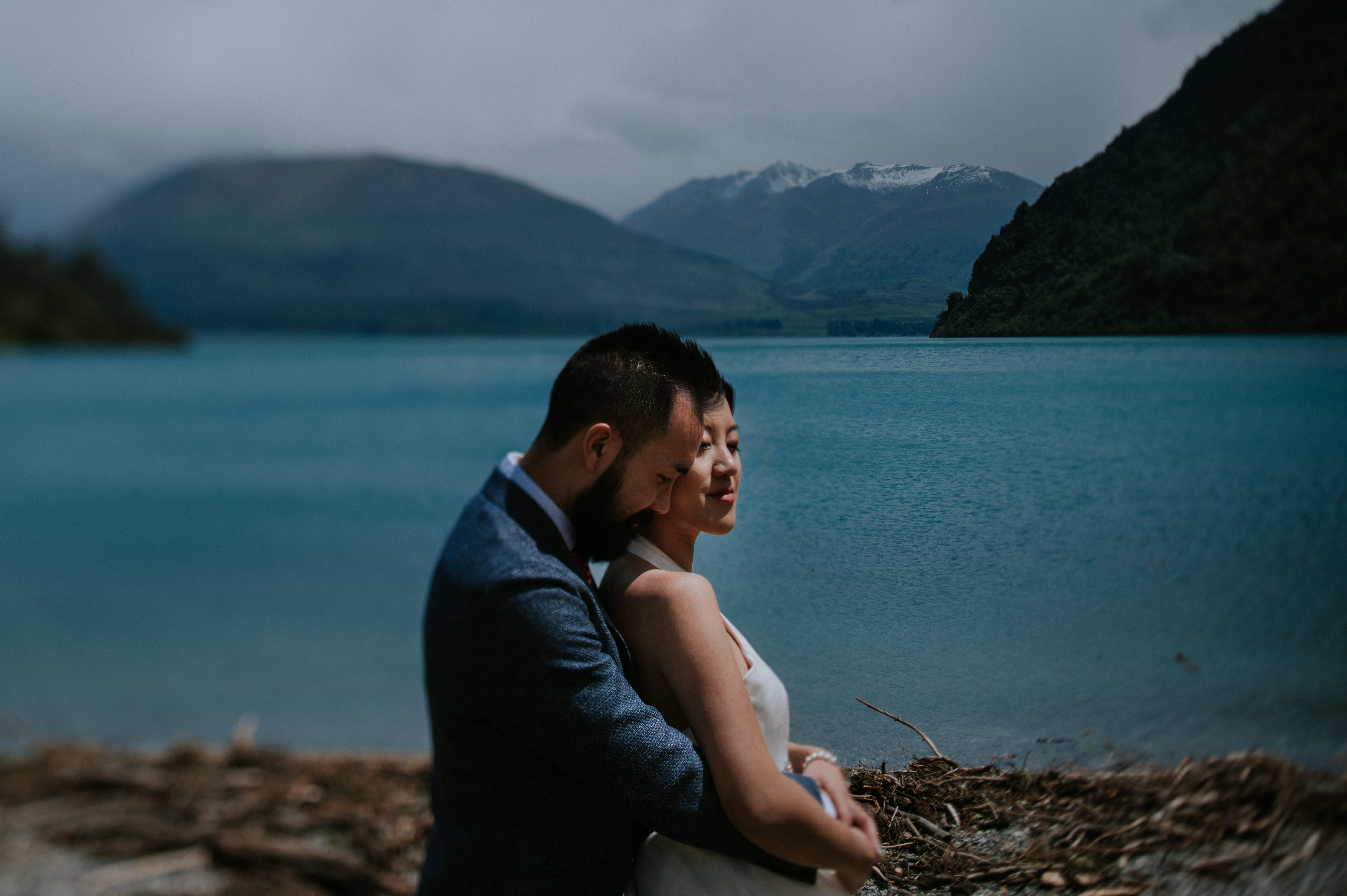 Couple embrace in at waterfront against mountains - photo by Charmi Pena