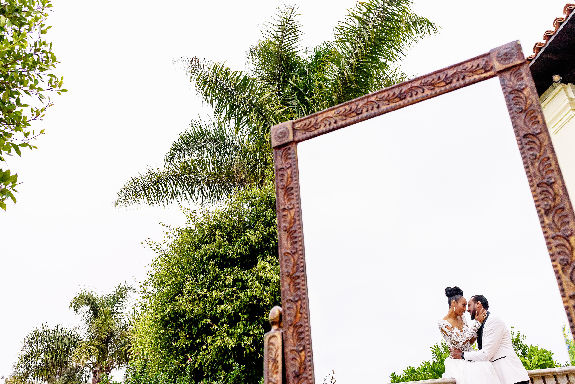Bride and groom reflected in outdoor mirror - photo by Kirth Bobb Photography