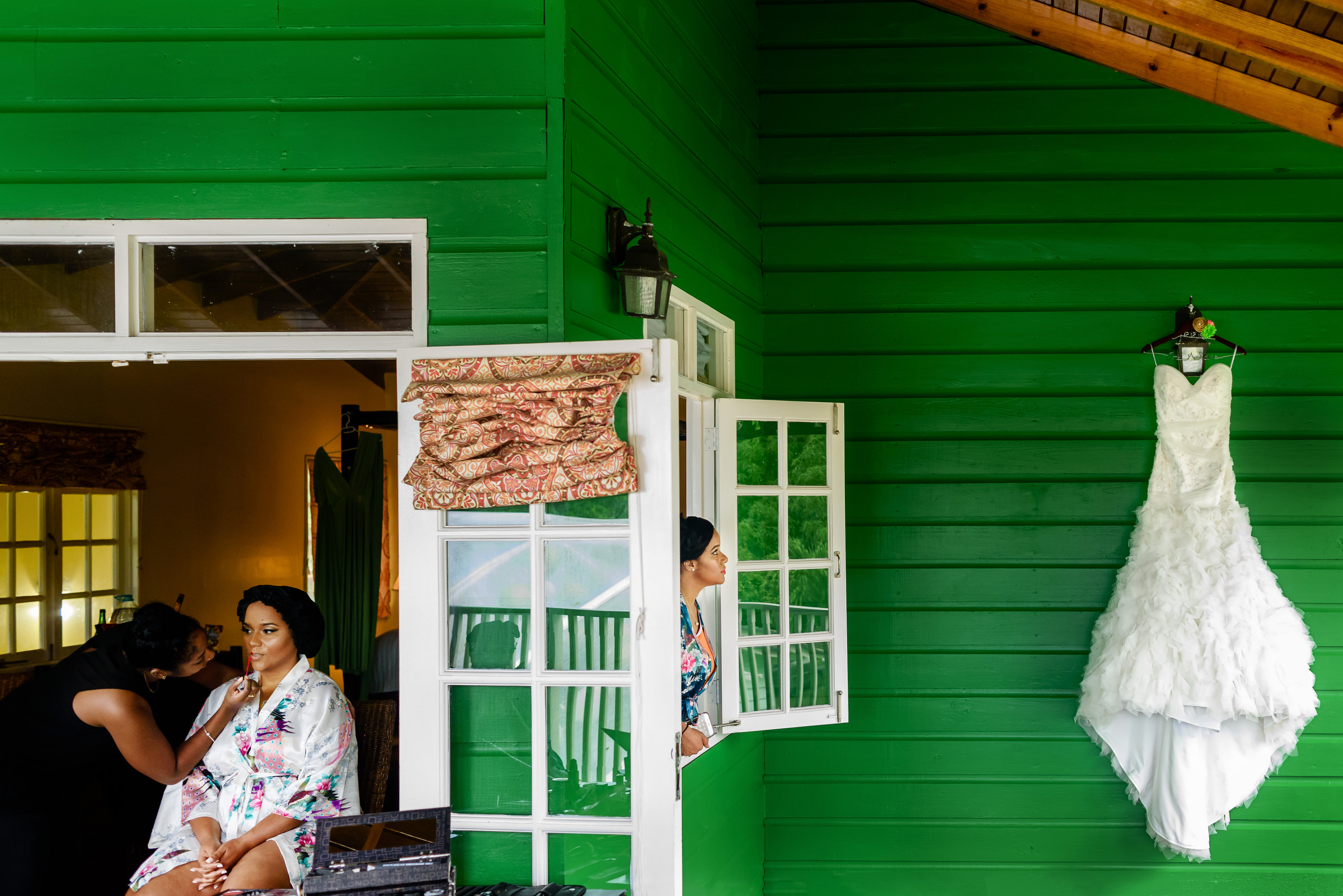 Bride having makeup applied dress hanging on green house in Jamaica  - photo by Kirth Bobb Photography