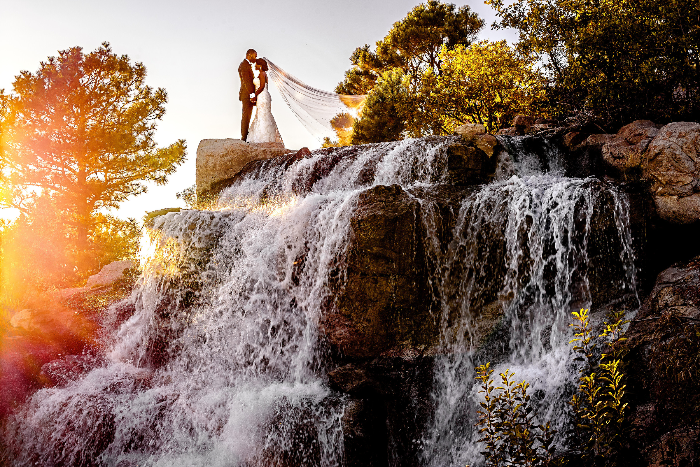 Couple face to face on top of sunlit waterfall - photo by Kirth Bobb Photography