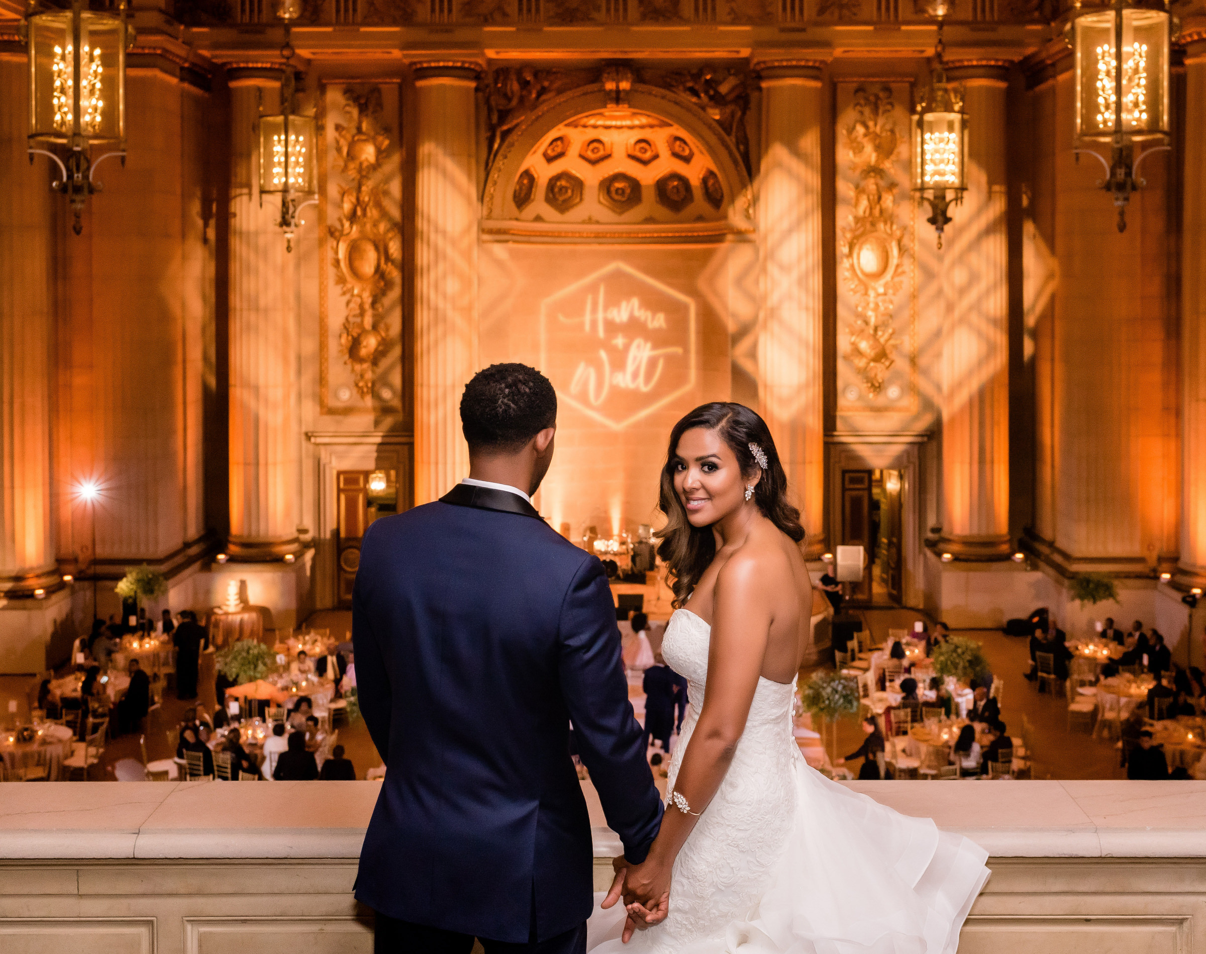 Couple looking down at reception tables from balcony - photo by Kirth Bobb Photography