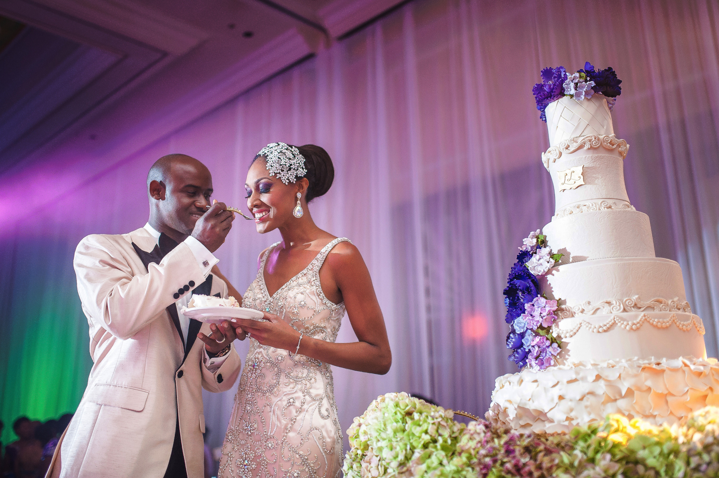Groom feeding the bride cake against 6 tiered cake- photo by Kirth Bobb Photography