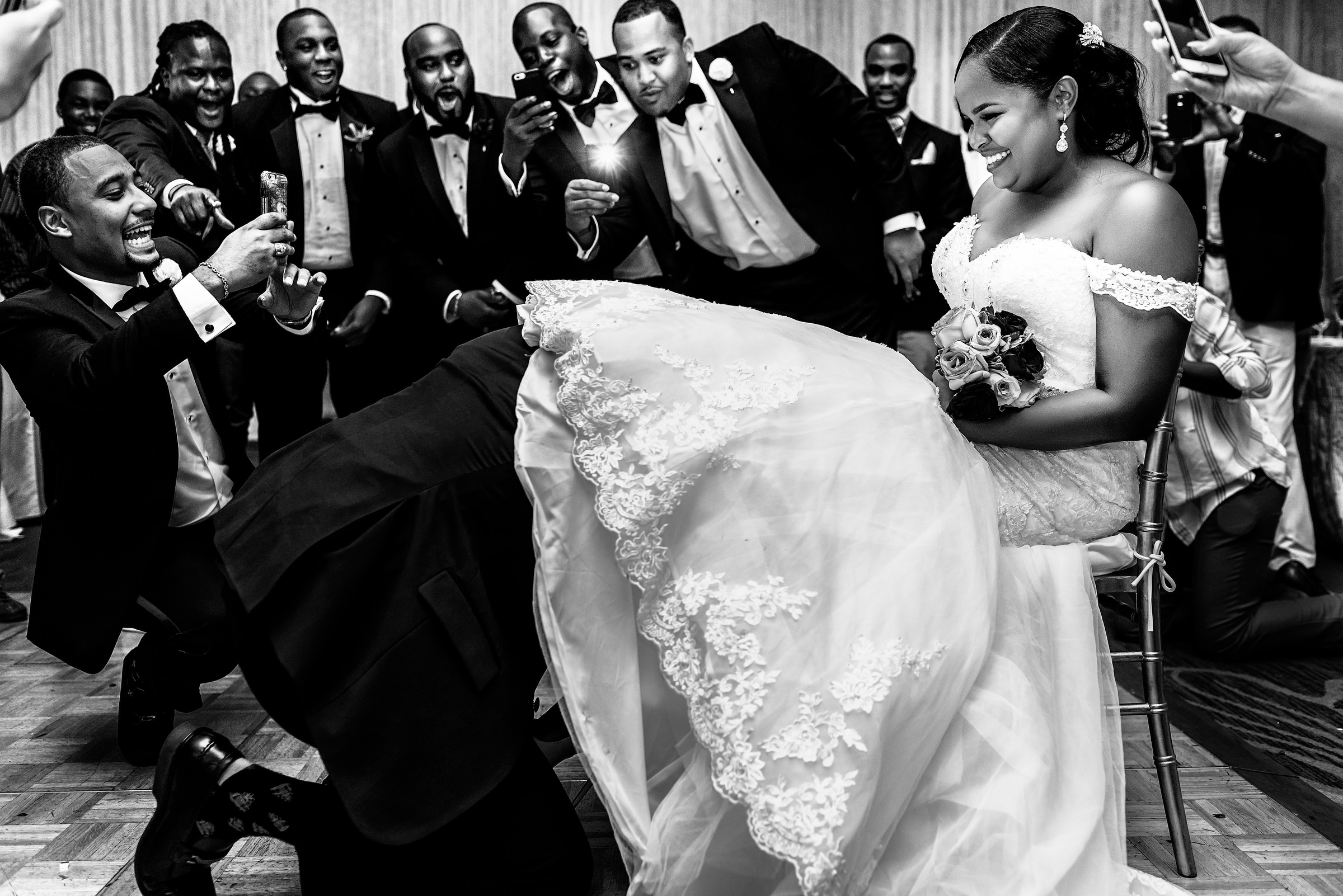 Groom hunting for bride's garter - photo by Kirth Bobb Photography