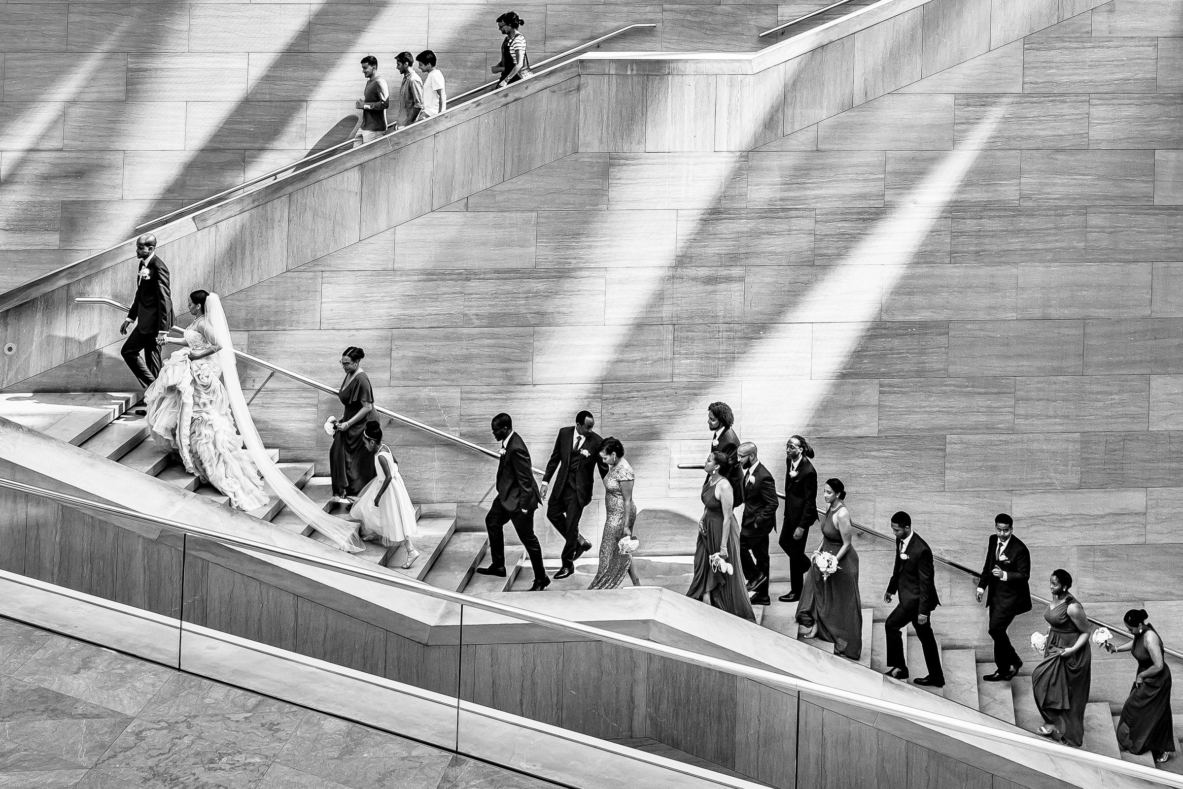 Group portrait of bride, groom, and bridal party ascending stairs - photo by Kirth Bobb Photography