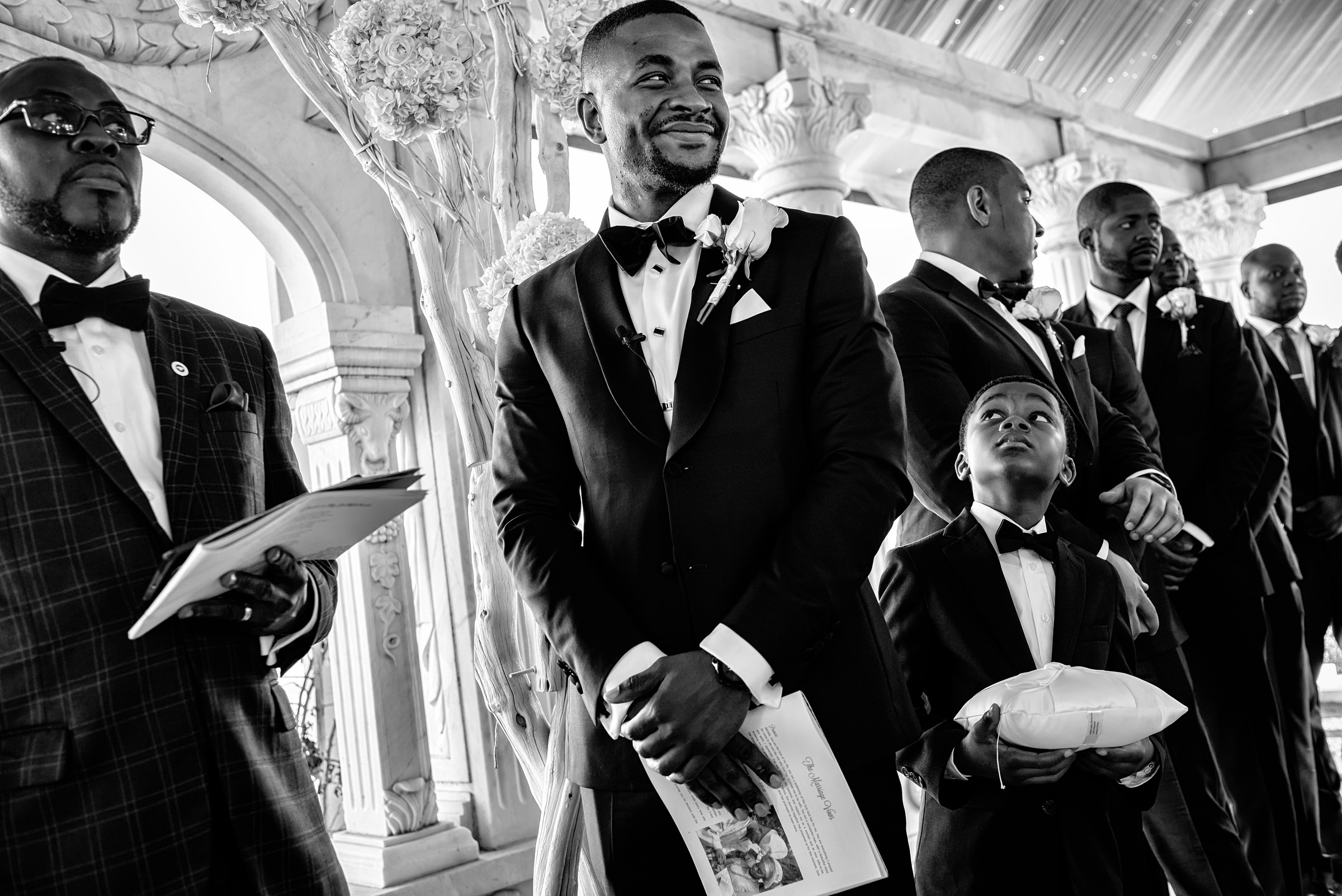 Young ringbearer looks up at smiling groom - photo by Kirth Bobb Photography