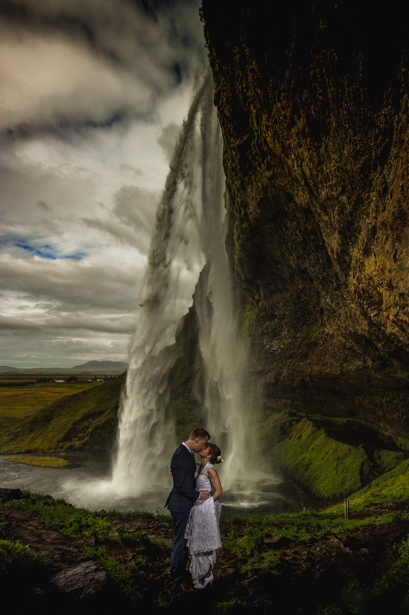 Couple face to face near large waterfall - photo by Viridian Images Photography